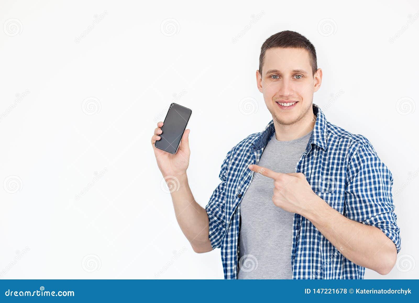Portret rozochocony, pozytywny, atrakcyjny facet z ściernią w koszula z smartphone z czarnym ekranem w jego ręce, punkt