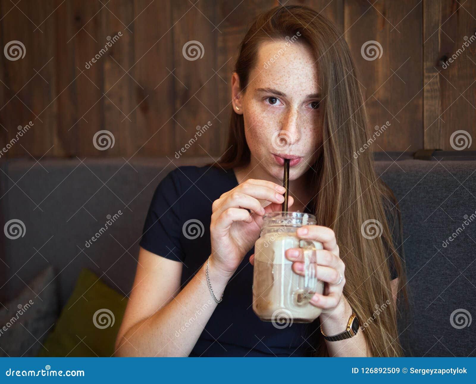Portret rudzielec młoda szczęśliwa piękna kobieta pije kawę w kawiarni przy kawową przerwą z piegami