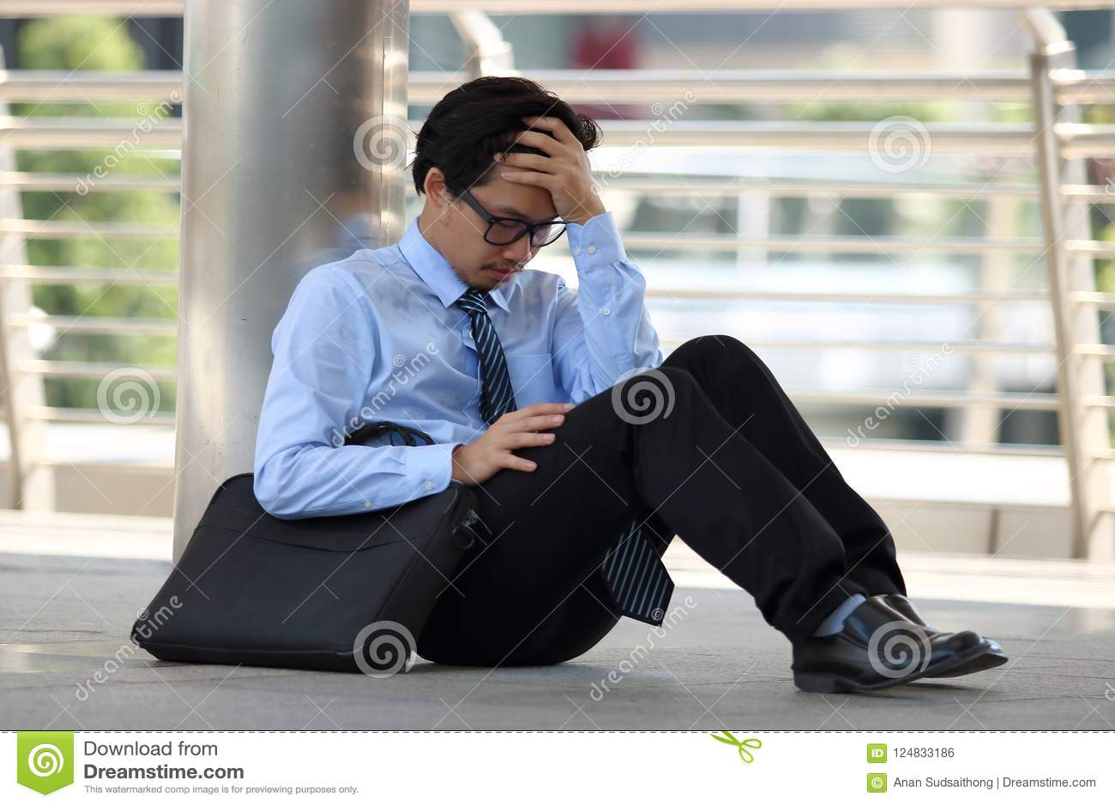 Portret sfrustowany zaakcentowany młody Azjatycki mężczyzna obsiadanie na podłoga chodniczka uczucie i biuro męczył z pracą