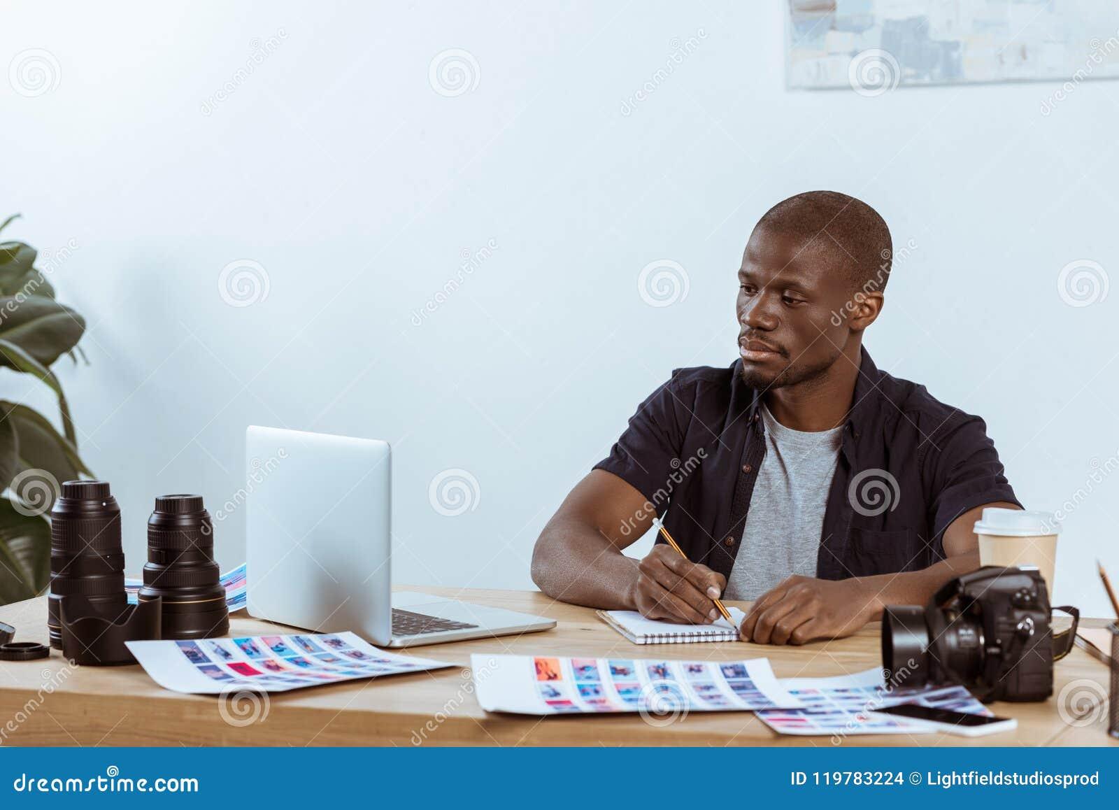 Portret skoncentrowany amerykanina afrykańskiego pochodzenia fotograf pracuje przy miejscem pracy z laptopem