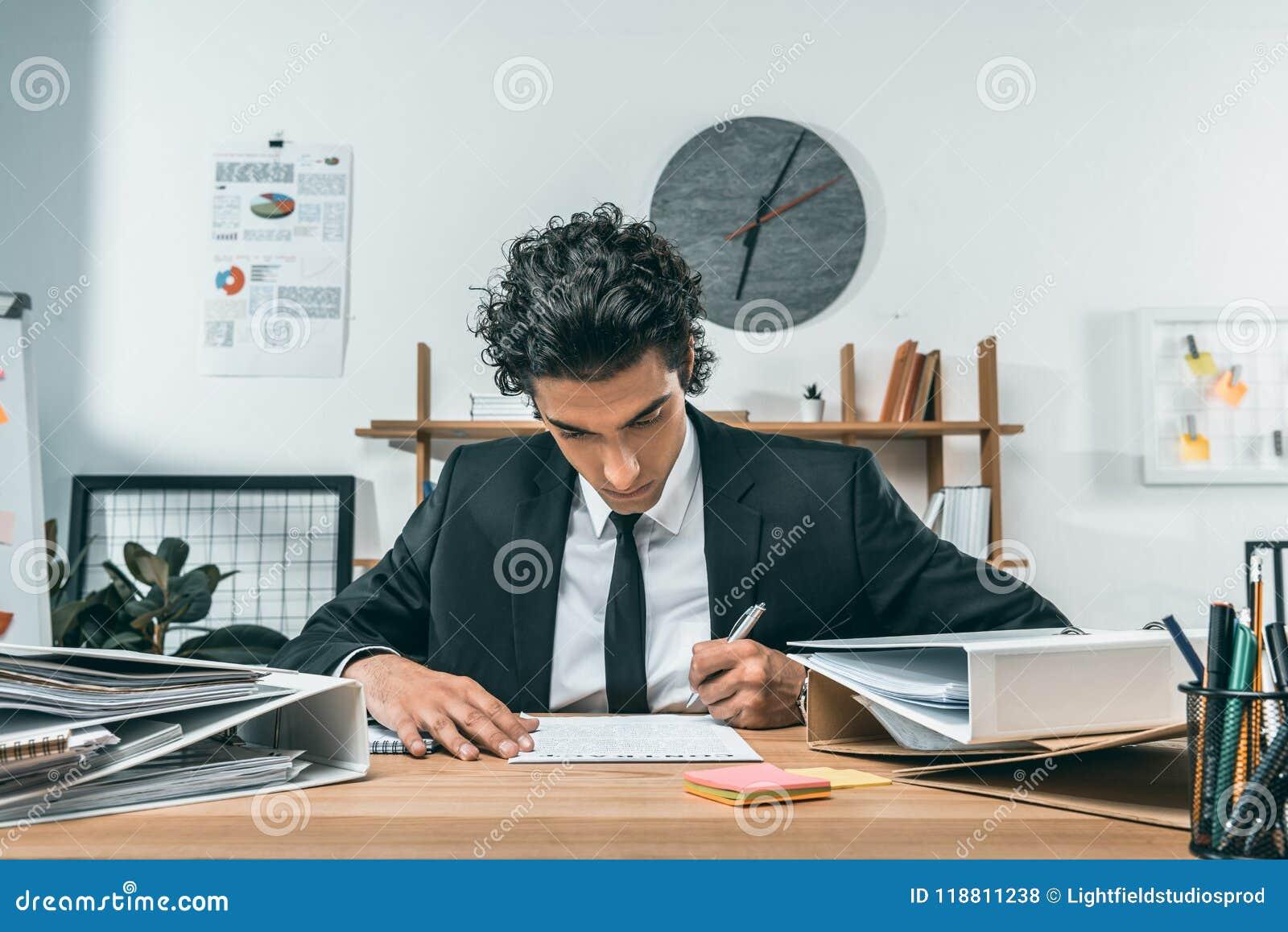 Portret skoncentrowany biznesmena writing pracy plan przy miejscem pracy