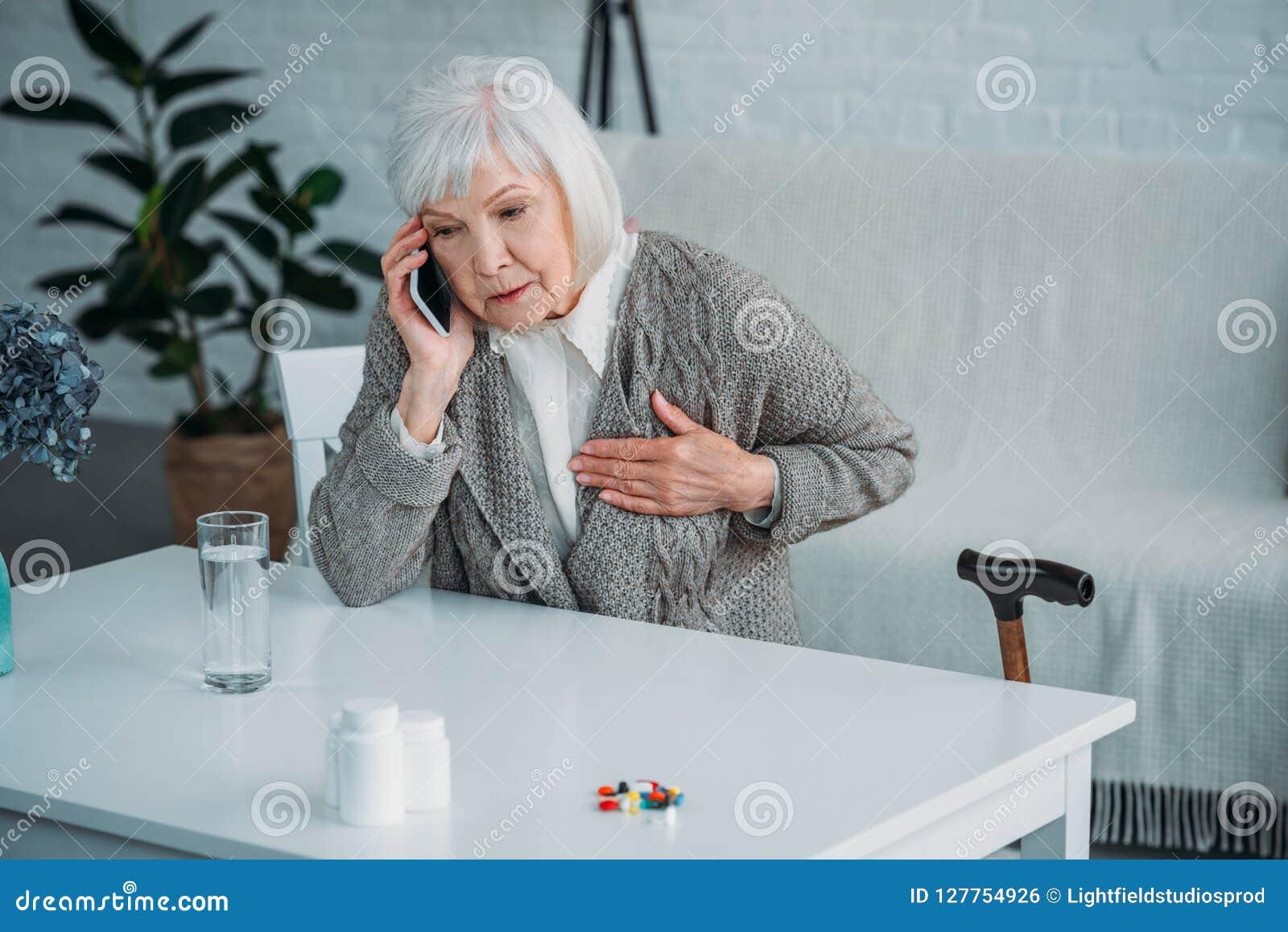 Portret starsza kobieta opowiada na smartphone przy stołem z medycynami z kierową obolałością