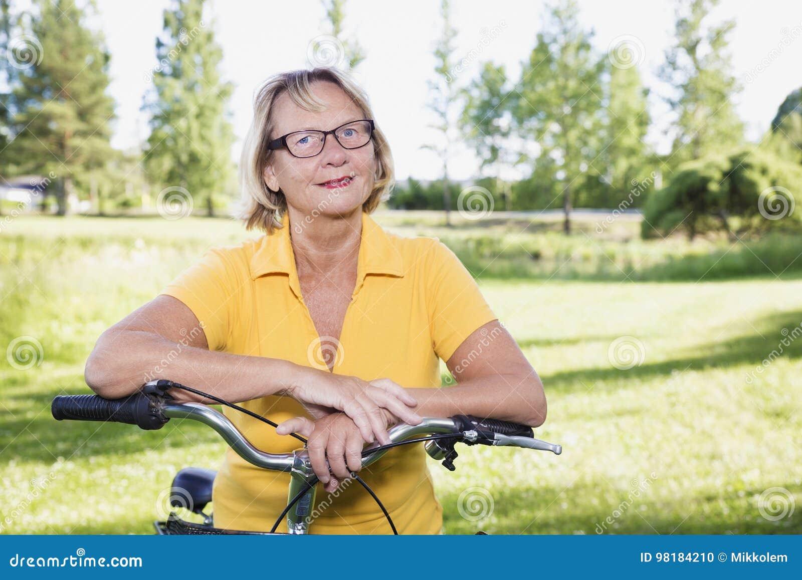 Portret starsza kobieta z bicyklem bierze przerwę