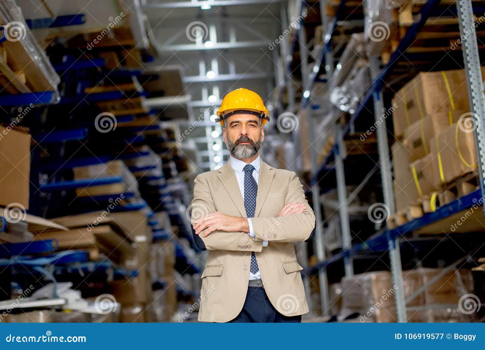 Portret starszy biznesmen w kostiumu z hełmem w warehous