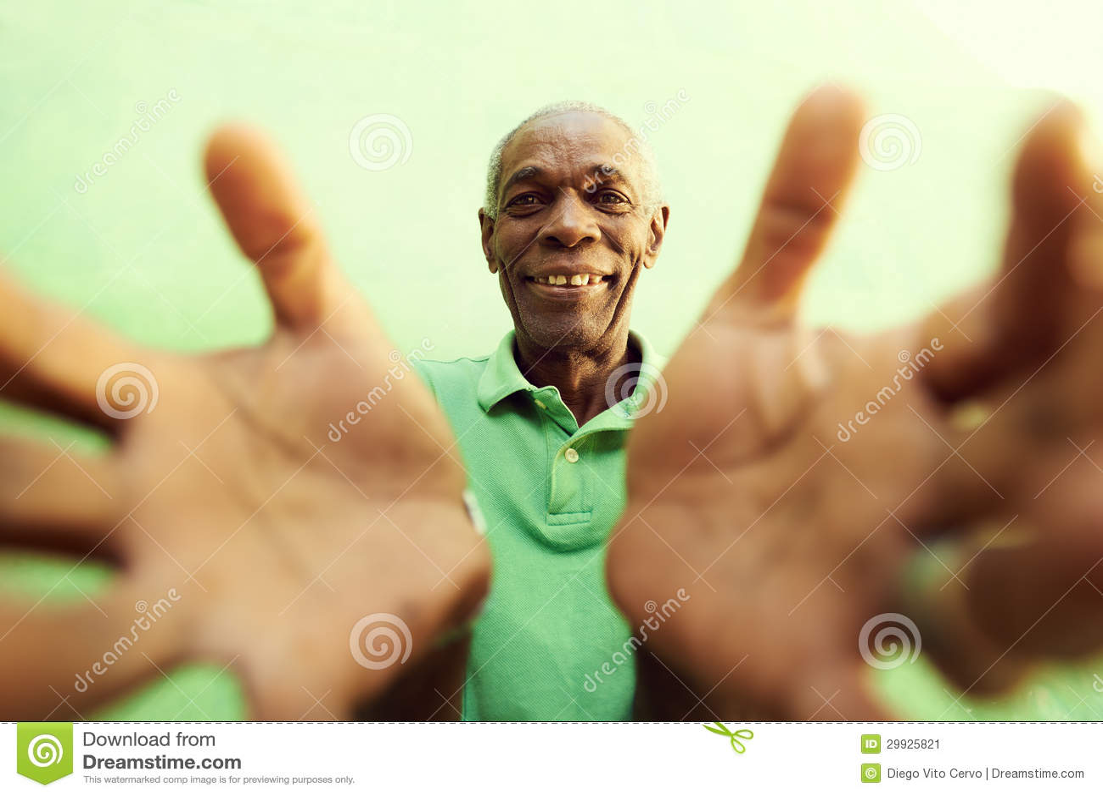 Stary afrykański mężczyzna z rękami i ręki otwieramy, obejmujący kamerę