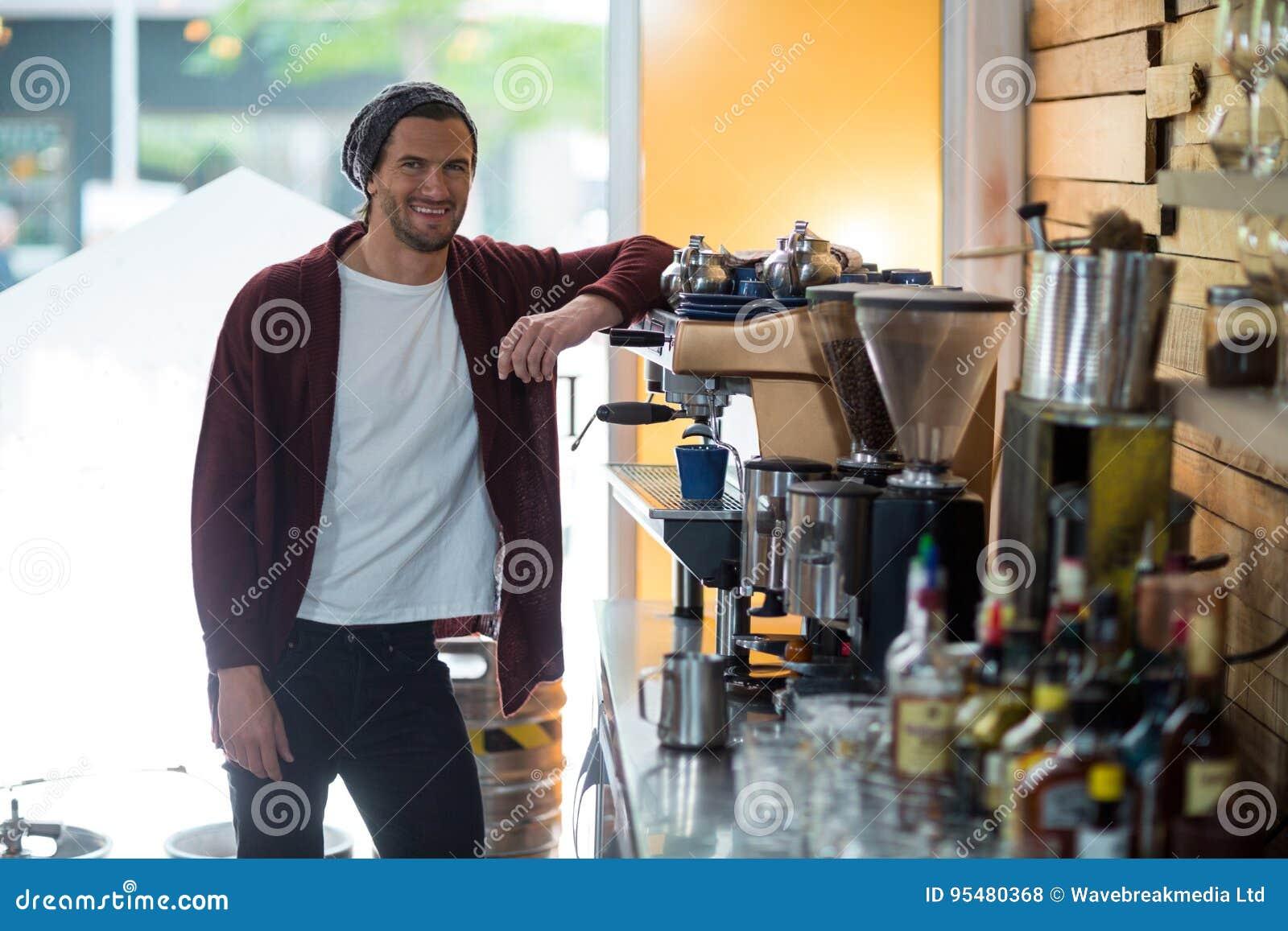 Portret stoi blisko kawy espresso maszyny uśmiechnięty właściciel