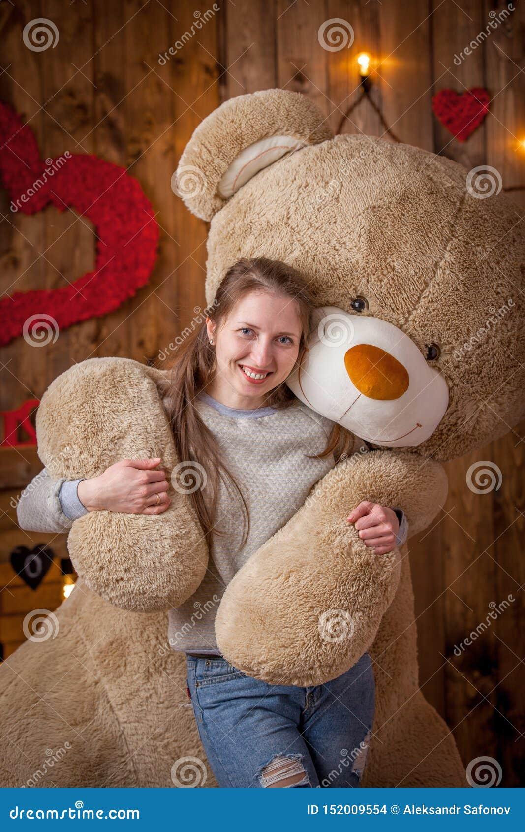 Portret szczęśliwa dziewczyna z ogromnym niedźwiedziem