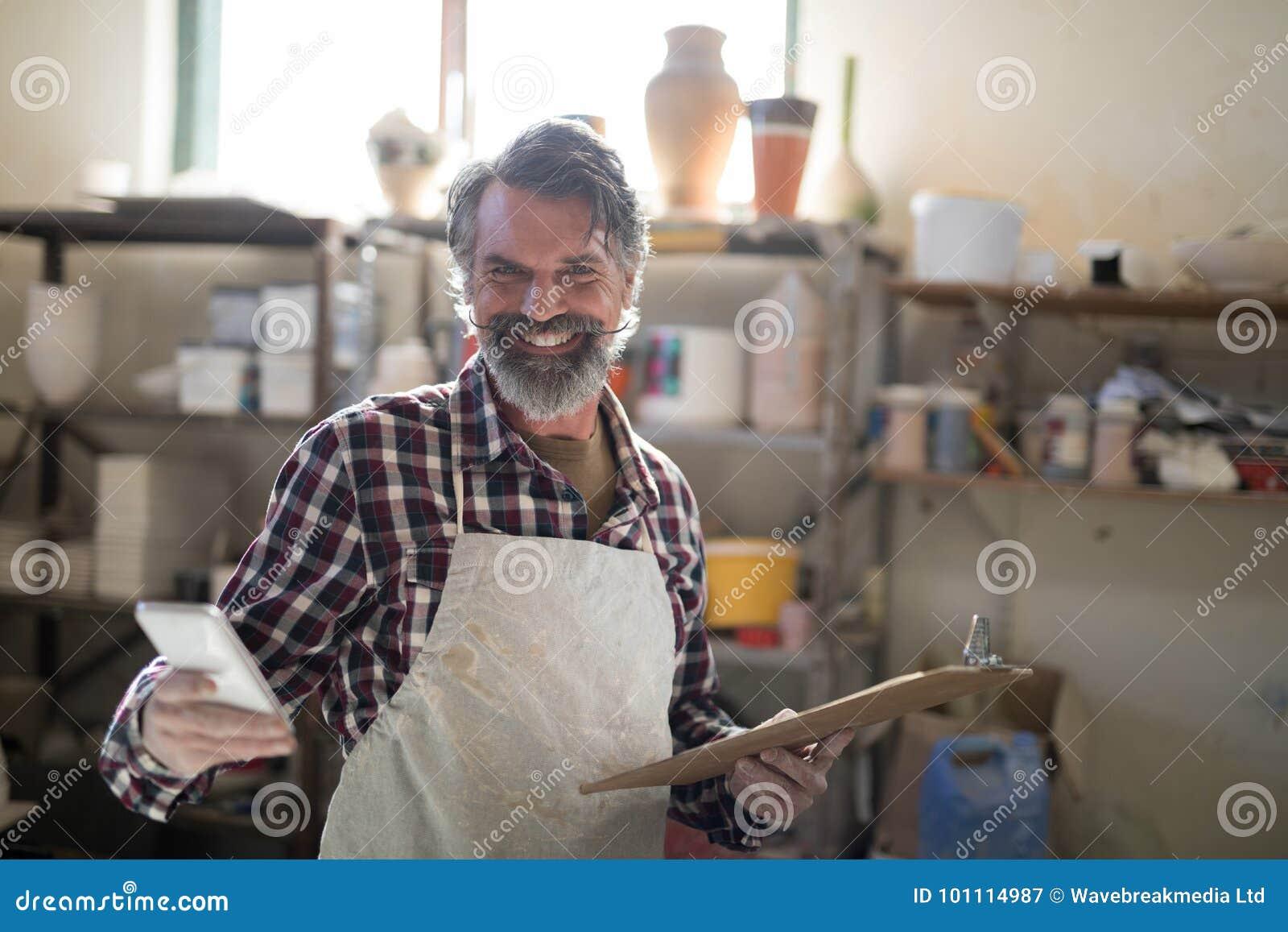 Portret szczęśliwa garncarka używa telefon komórkowego