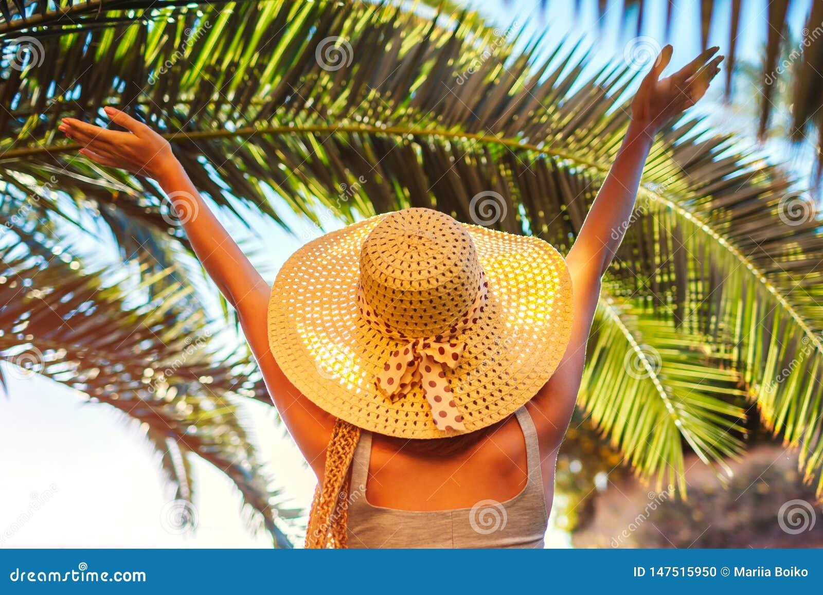 Portret szczęśliwa kobieta w kapeluszowych udźwig rękach pod palmowym liściem w hotelowym jardzie katya lata terytorium krasnodar