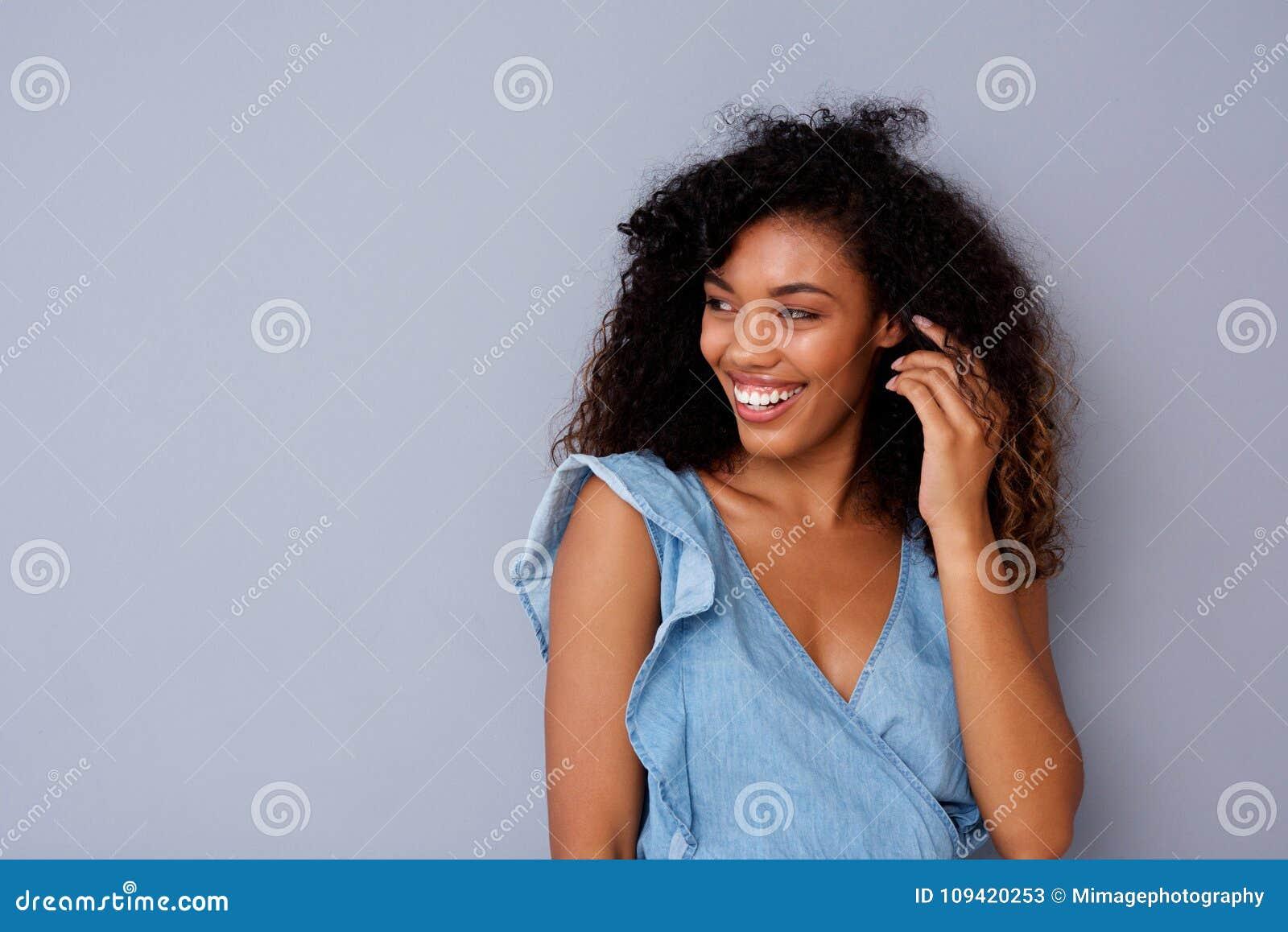Portret szczęśliwa młoda amerykanin afrykańskiego pochodzenia kobieta ono uśmiecha się przeciw szaremu tłu