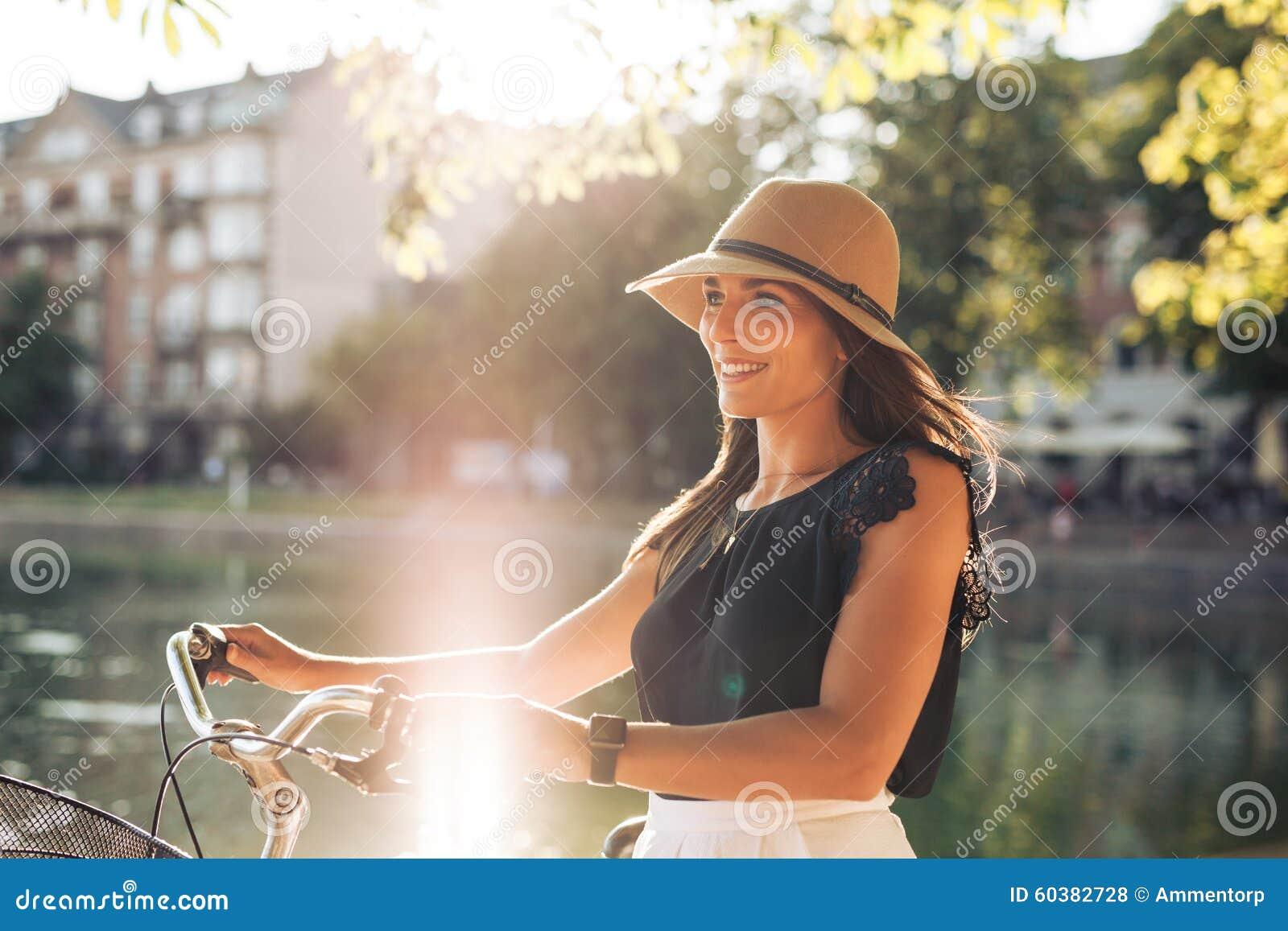Portret szczęśliwa młoda kobieta przy miasto parka odprowadzeniem z jej bicyklem
