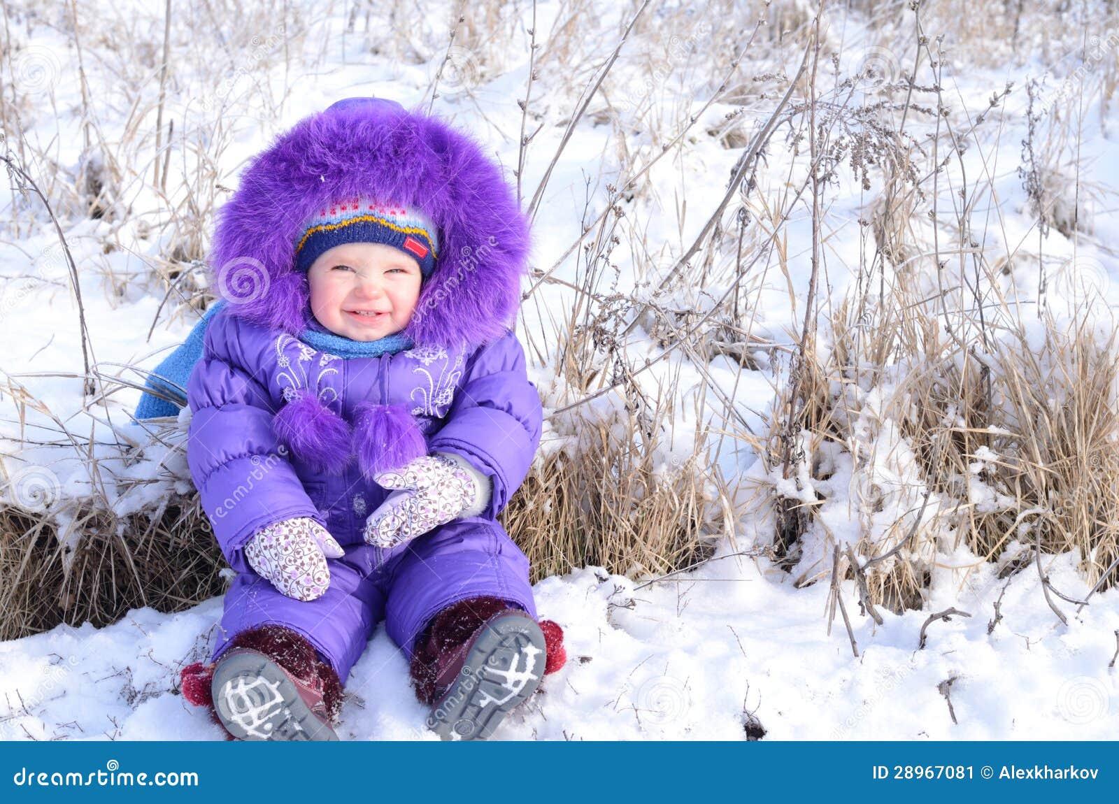 Portret szczęśliwa mała dziewczynka w śnieżnym krajobrazie