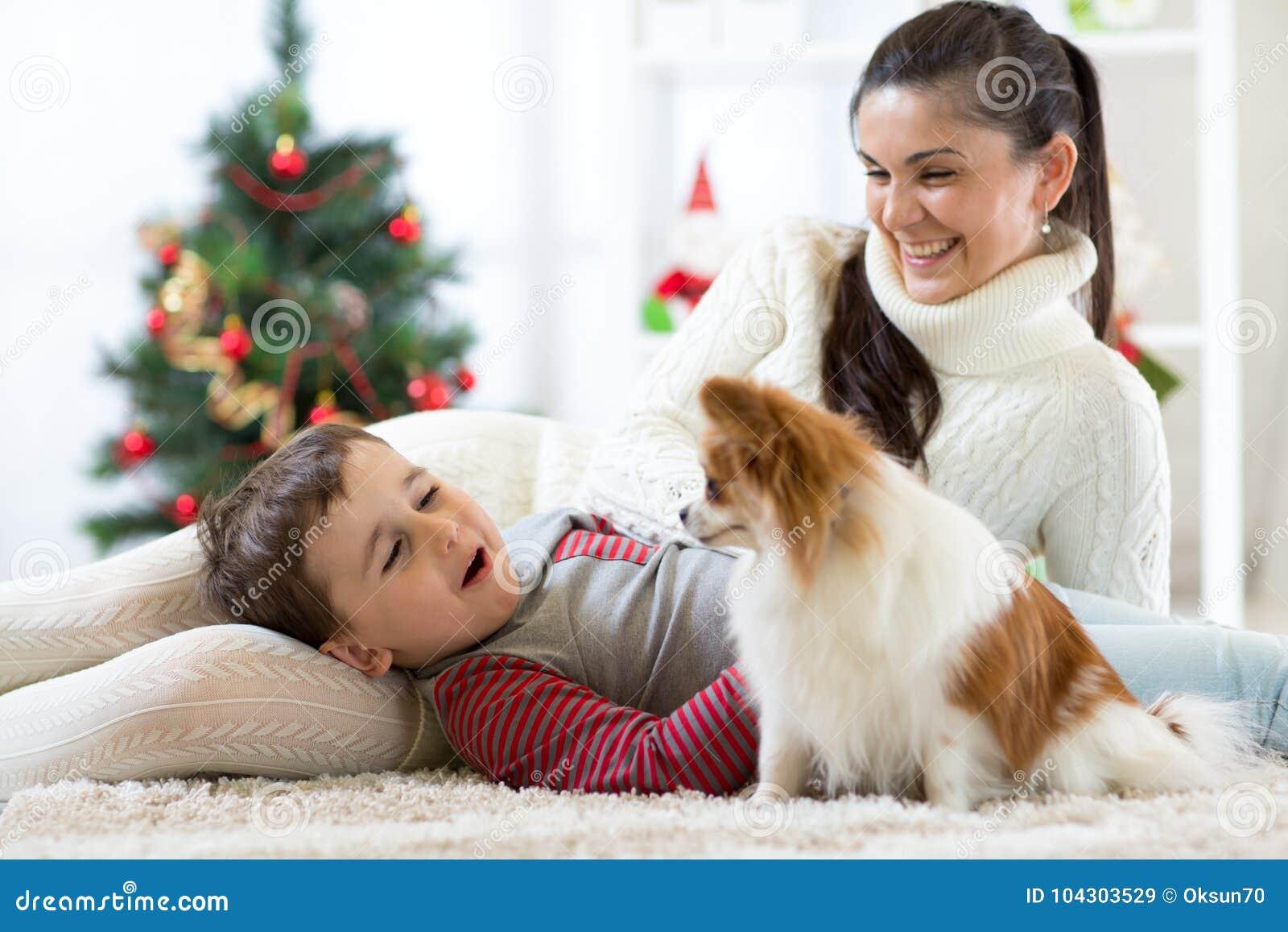 Portret szczęśliwa matka i jej mały syn z psim wydający wpólnie Bożenarodzeniowego czas w domu blisko mas drzewa