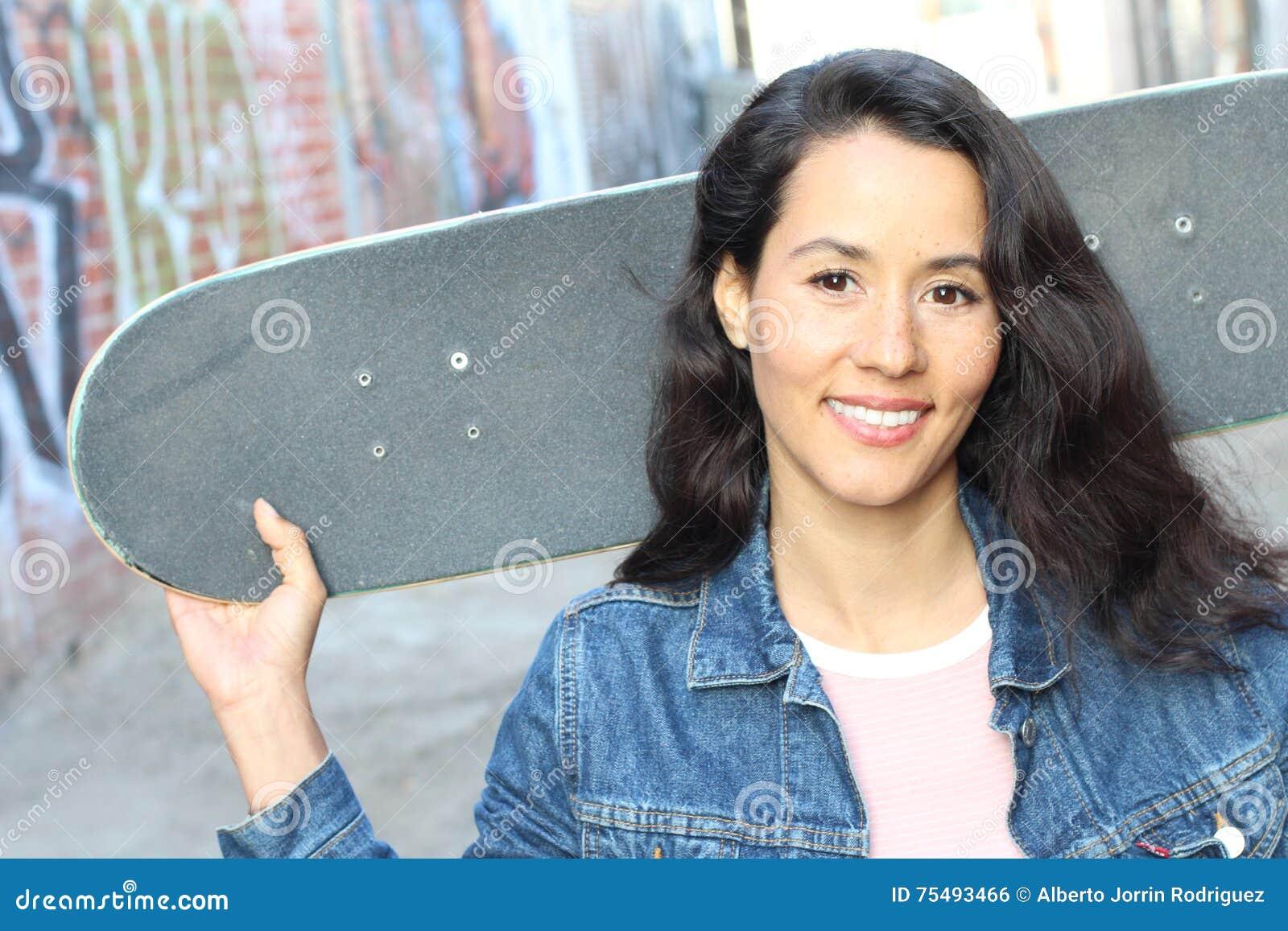 Portret szczęśliwa piękna kobieta patrzeje w kamerę z długim seksownym zdrowym włosy w drelichowej kurtce z jej deskorolka