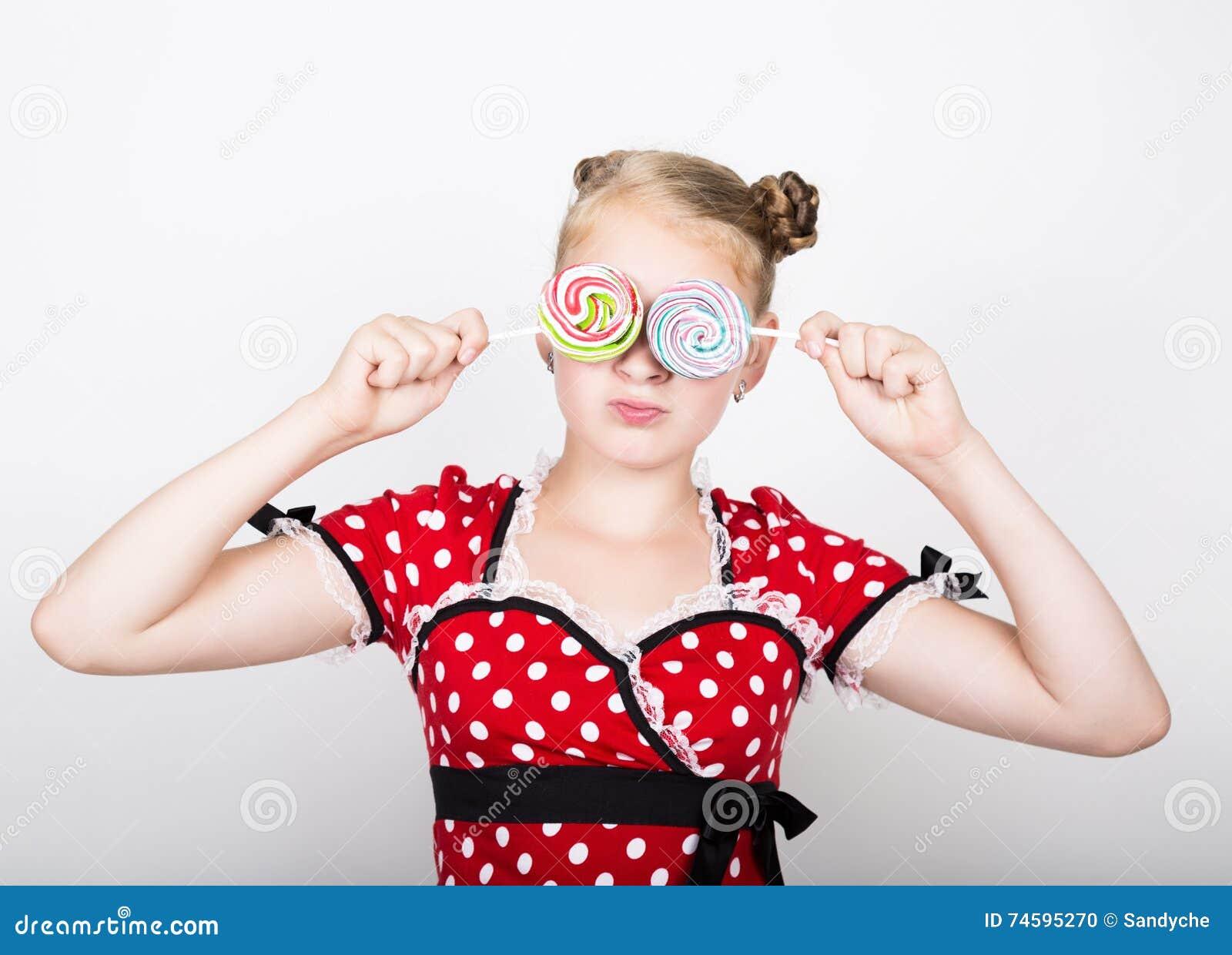 Portret szczęśliwa piękna młoda dziewczyna z słodkimi candys ładna młoda kobieta ubierał w czerwonej sukni z białą polką