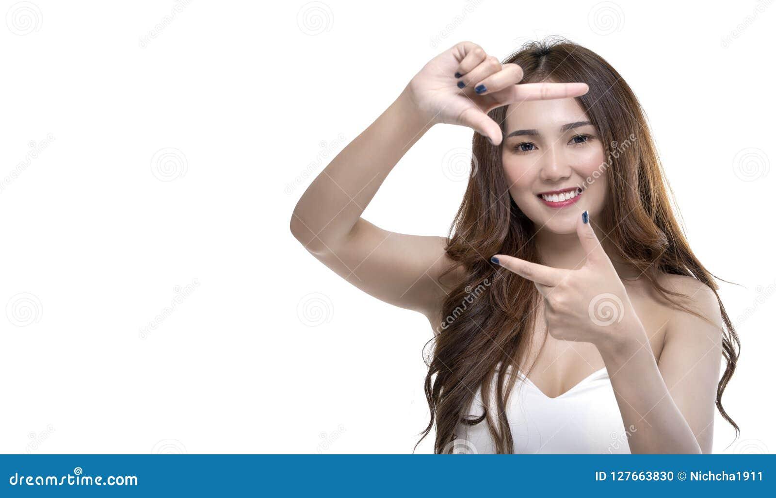 Portret szczęśliwa pozytywna młoda azjatykcia dziewczyna robi ramowemu round gestykuluje aktywnie przy kamerą