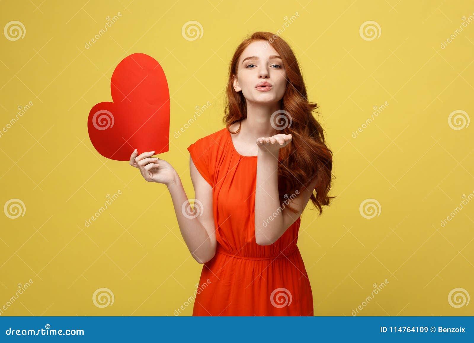 Portret szczęśliwa romantyczna młoda caucasian dziewczyna z czerwień papieru sercowatą pocztówką, romantyczni życzenia, walentynk