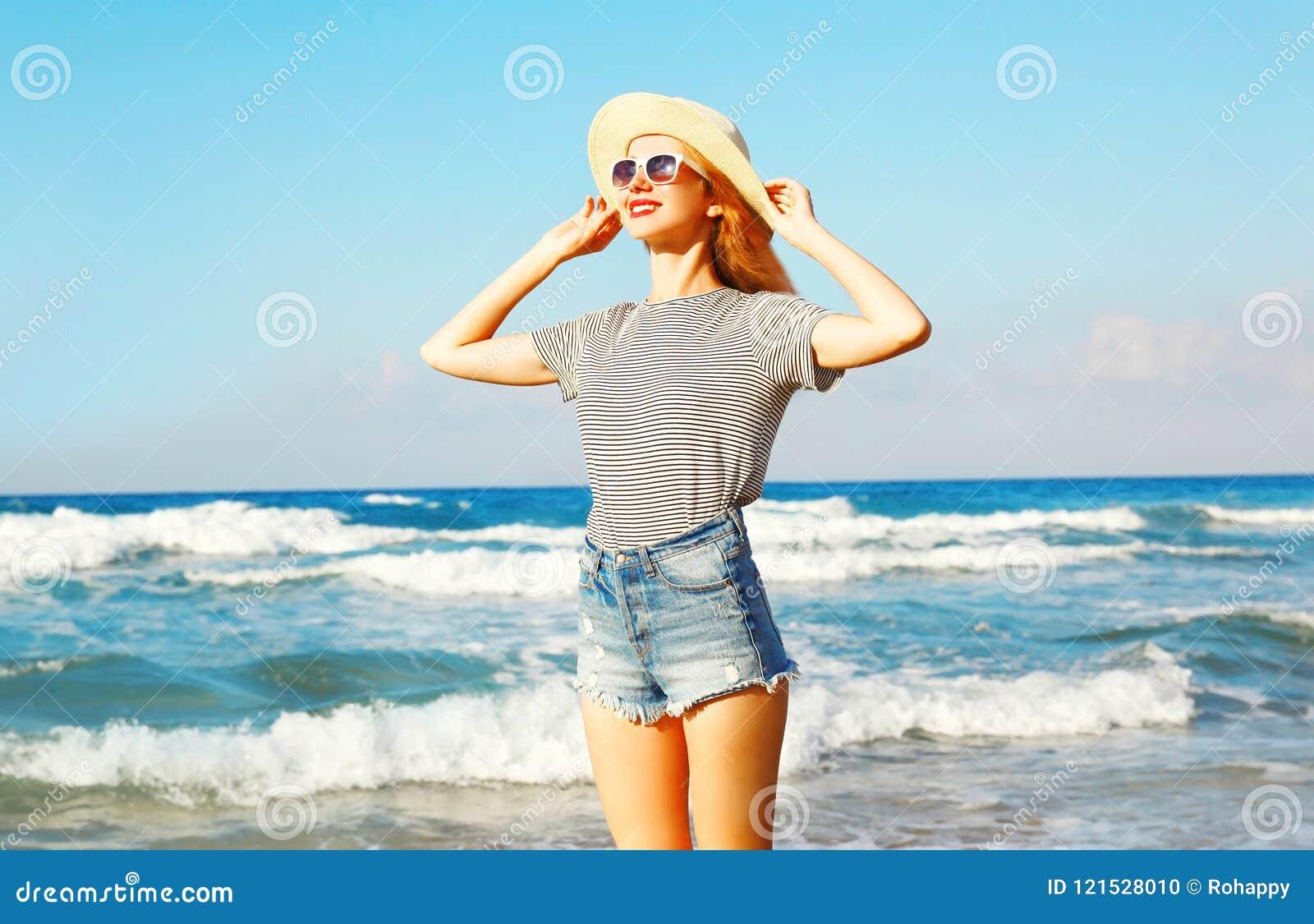 Portret szczęśliwa uśmiechnięta kobieta na plaży nad morzem przy latem