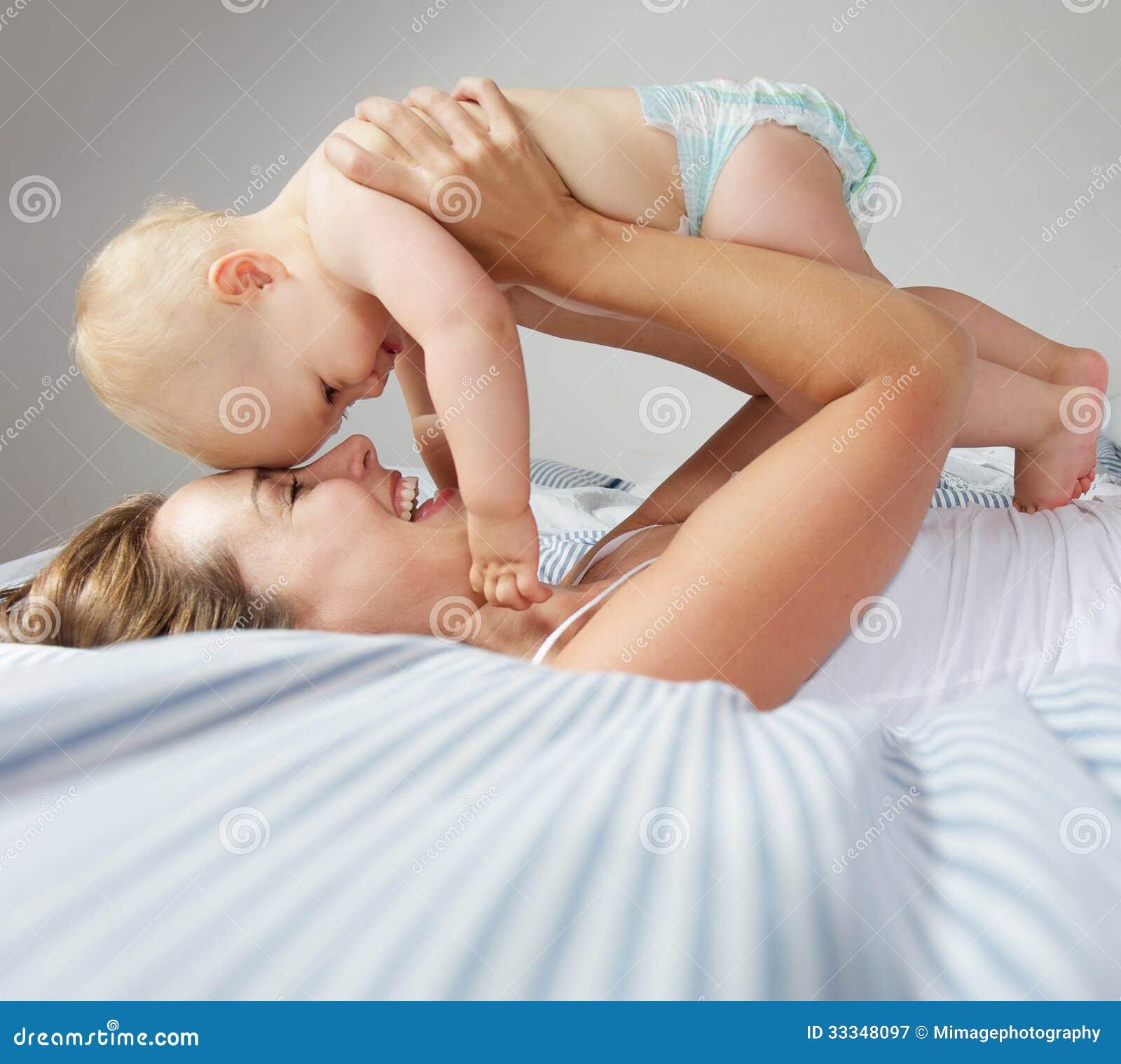 Portret szczęśliwi potomstwa matkuje ściskać ślicznego dziecka