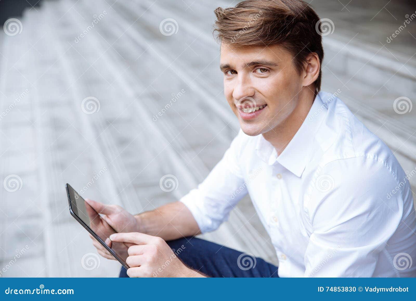 Portret szczęśliwy biznesmen używa pastylkę outdoors