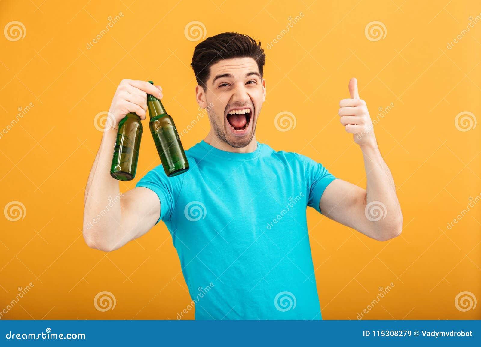 Portret szczęśliwy młody człowiek w koszulki mienia piwie