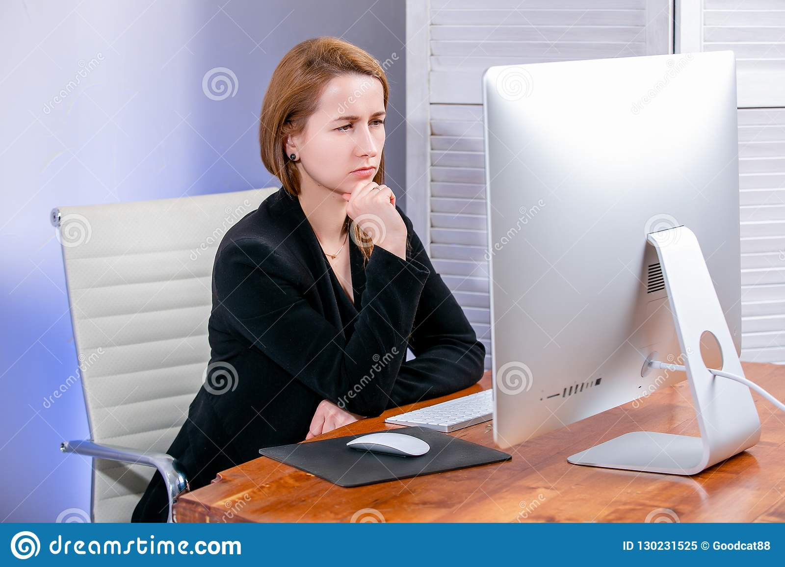 Portret szczęśliwy młody pomyślny bizneswoman przy biurem Siedzi przy spojrzeniami przy pokazem i stołem ostrożnie czarny Piątek