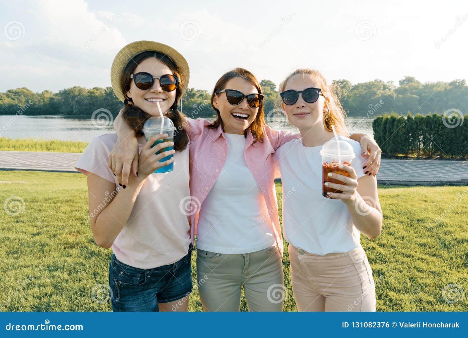 Portret szczęśliwy matki, córek nastolatków lat i, dziewczyny z lato napojami Tło natura, rekreacyjny teren