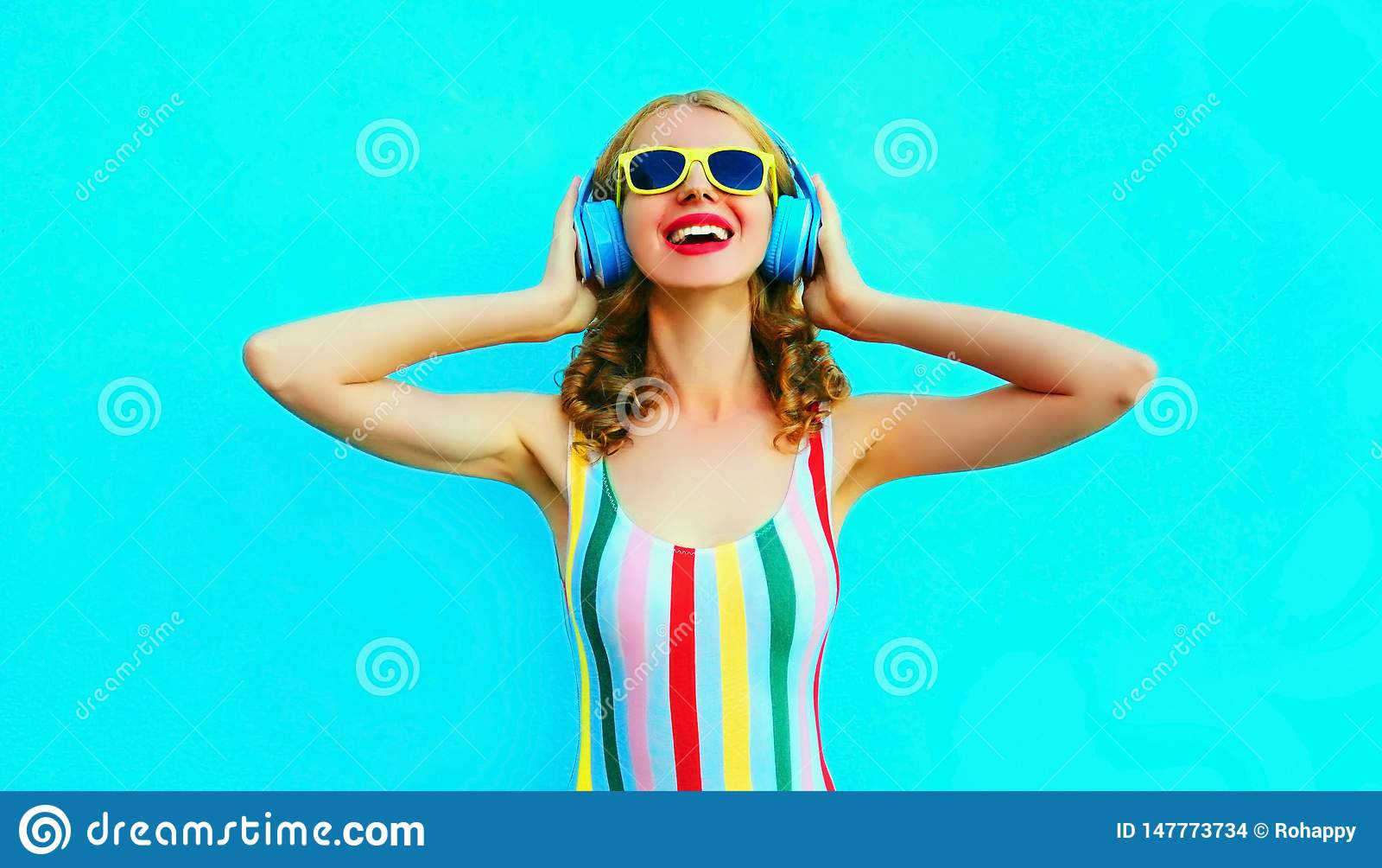 Portret szcz??liwa u?miechni?ta kobieta s?ucha muzyka w bezprzewodowych he?mofonach na kolorowym b??kicie