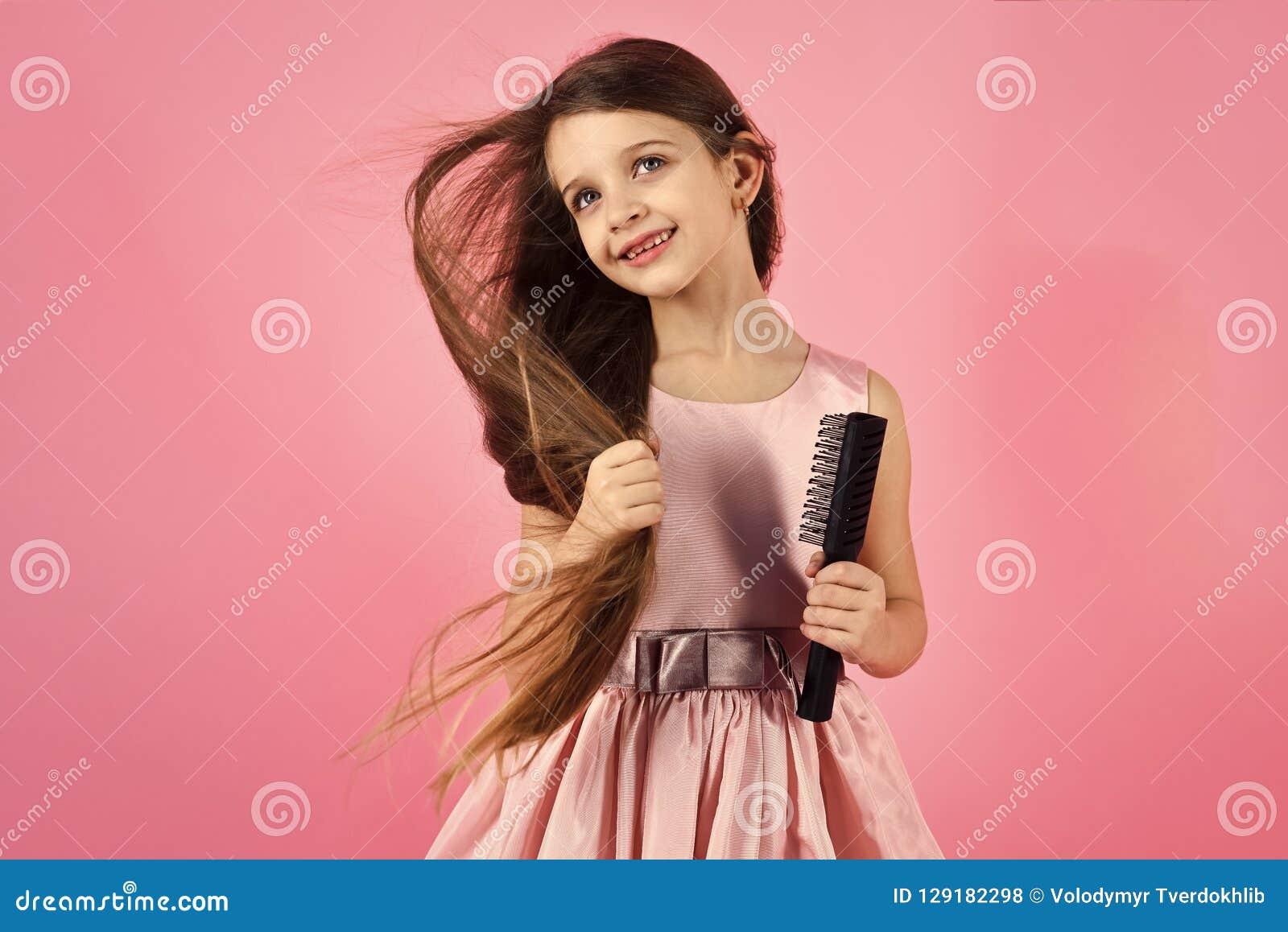 Portret szczotkuje jej włosy uśmiechnięta mała dziewczynka