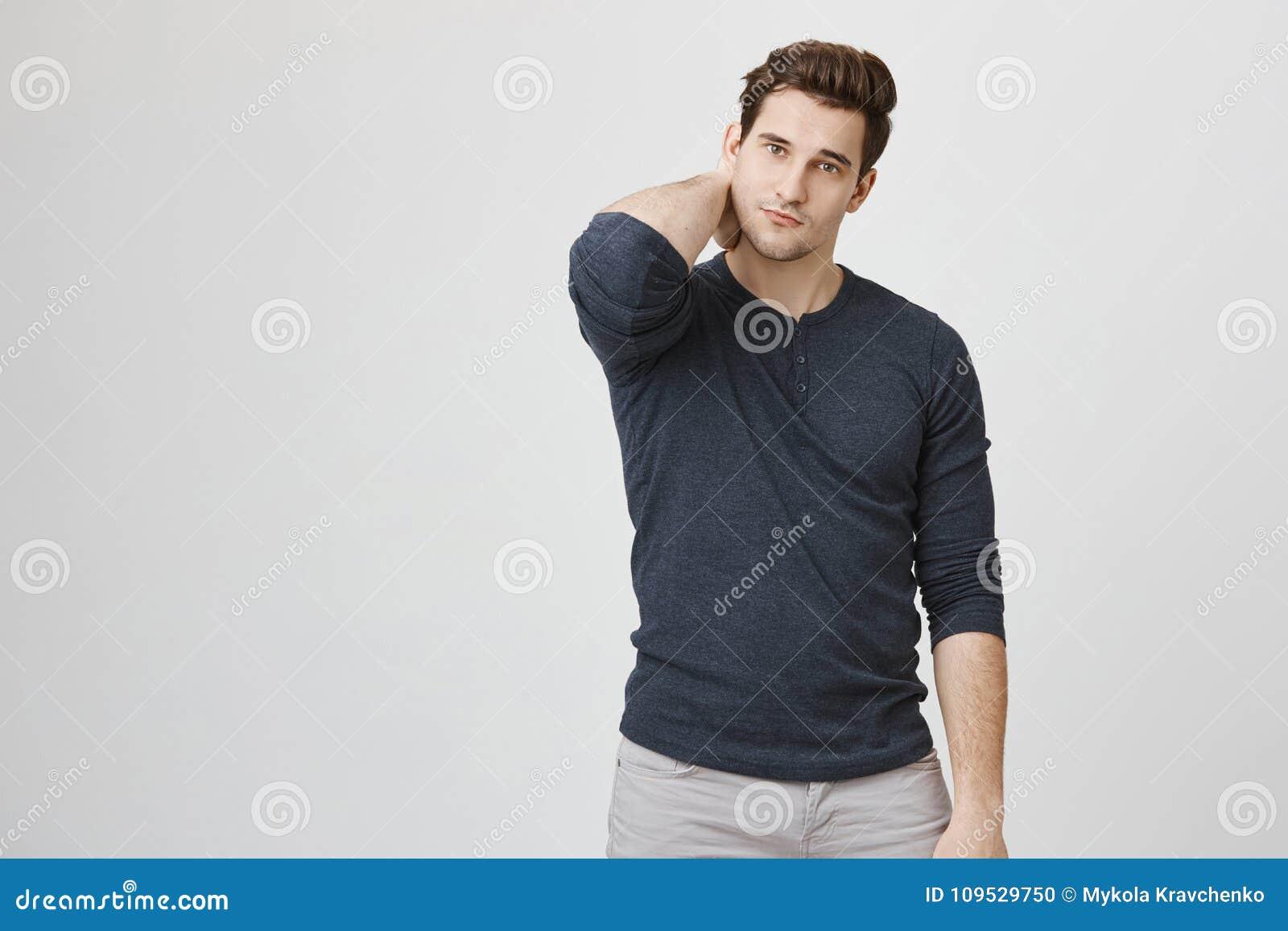 Portret szczupły przystojny mężczyzna drapa jego szyję i patrzeje kamerę czuje unconfident, odosobnionego nadmiernego biel,