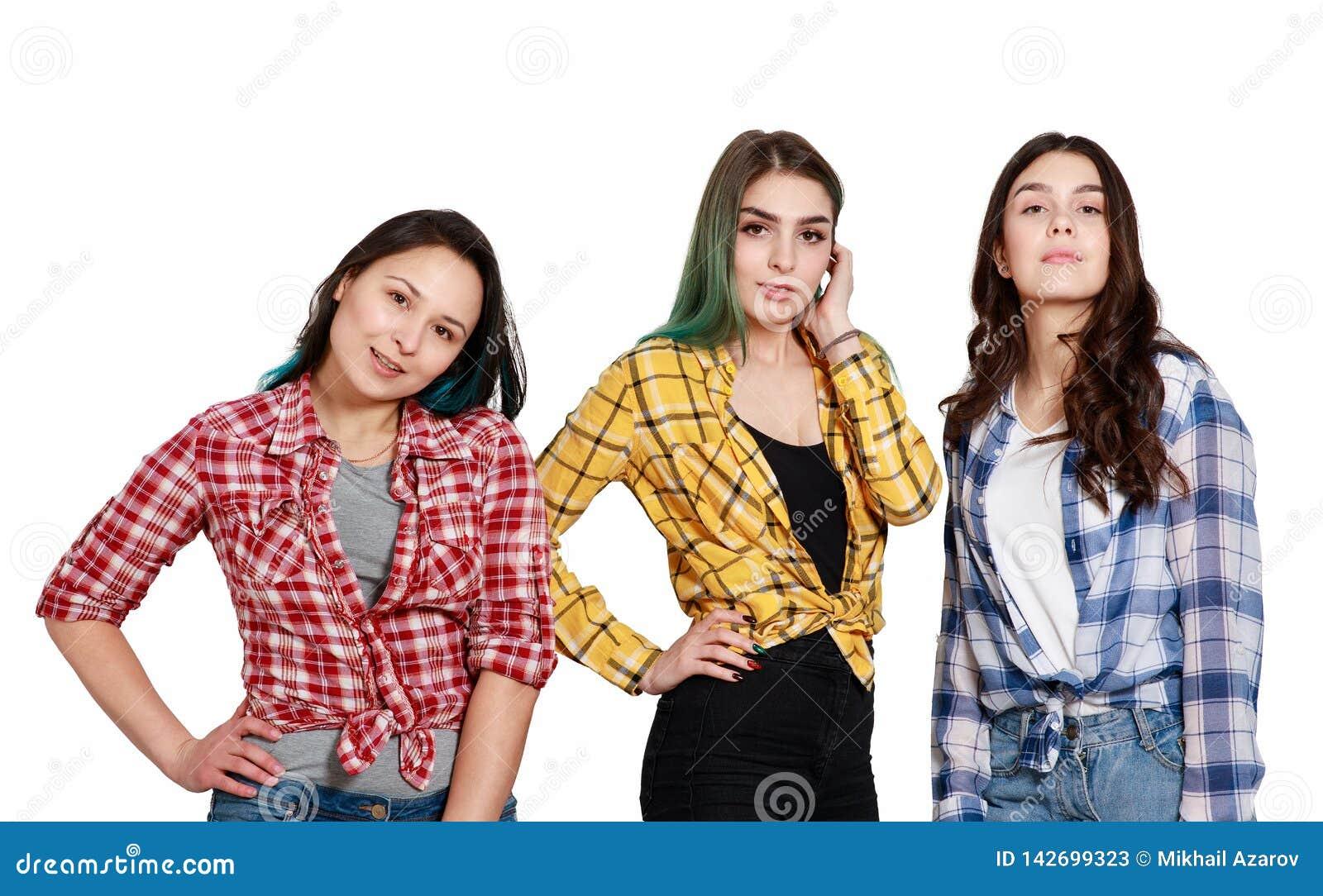 Portret trzy młodej pięknej nikłej dziewczyny kobiety w szkockich krat koszula czerwień, kolor żółty i błękit, Odizolowywający na