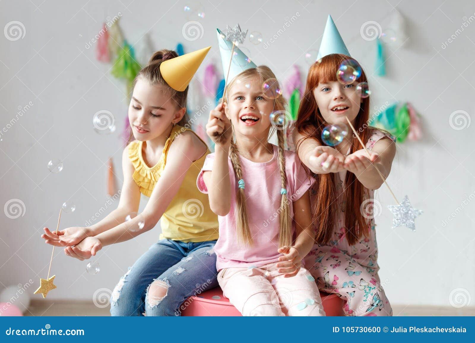 Portret trzy pięknej dziewczyny jest ubranym świąteczne nakrętki, bawić się z bąblami, siedzi wpólnie na krześle, świętuje urodzi