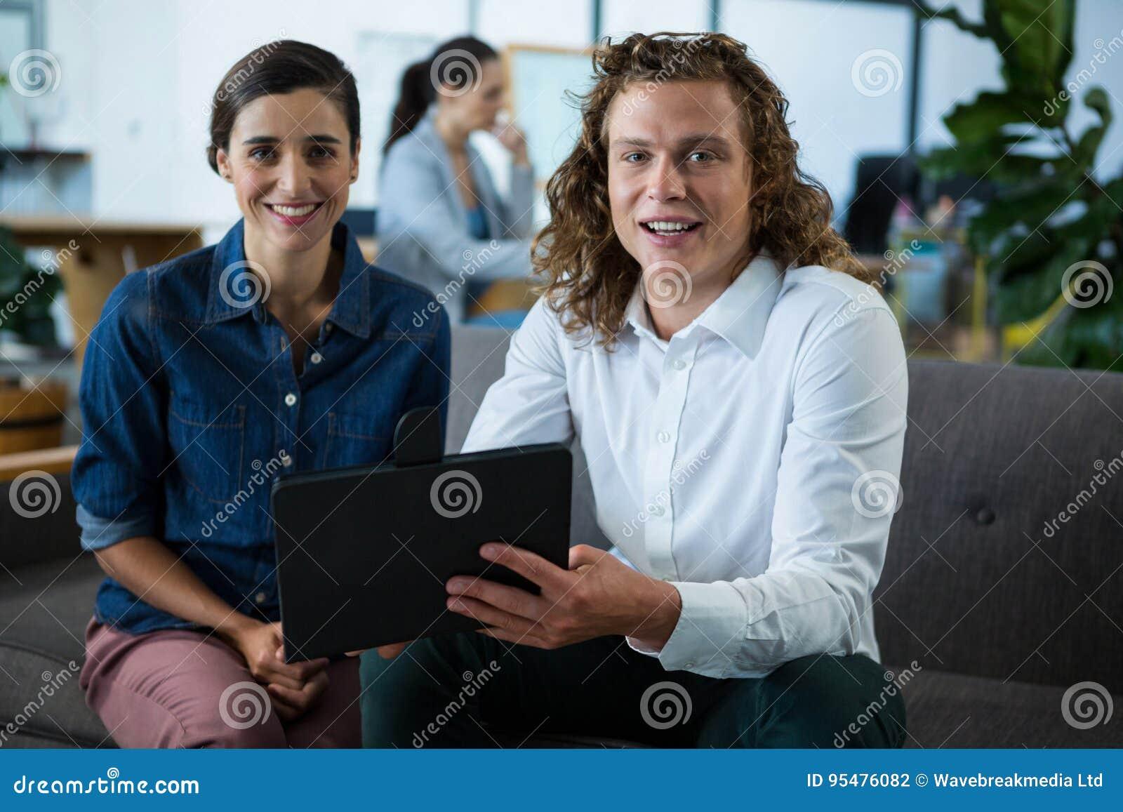 Portret uśmiechnięci biznesowi koledzy dyskutuje nad cyfrową pastylką