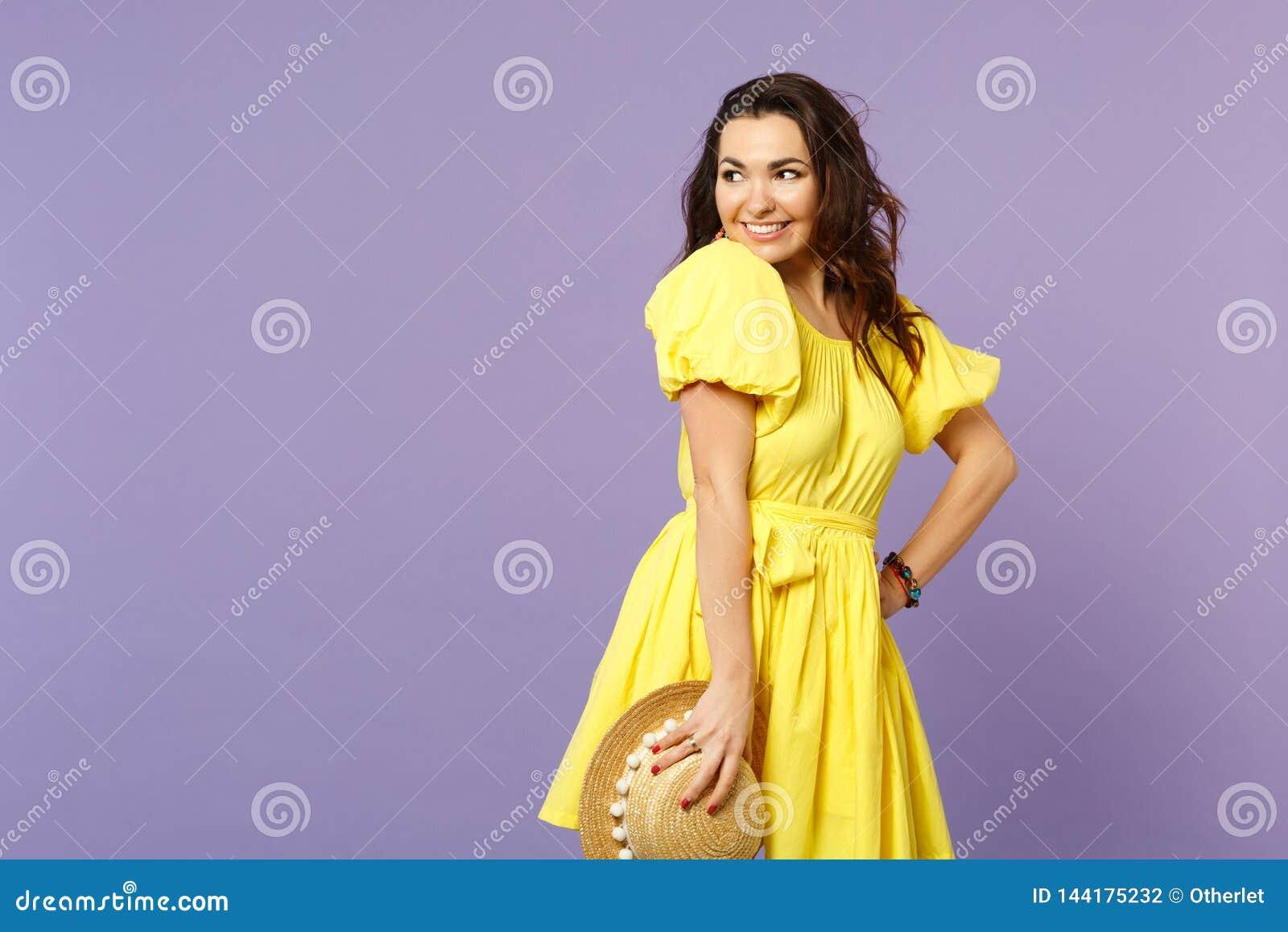 Portret uśmiechnięta ładna młoda kobieta w kolor żółty sukni mienia lata kapeluszu, patrzeje na boku na pastelowym fiołku