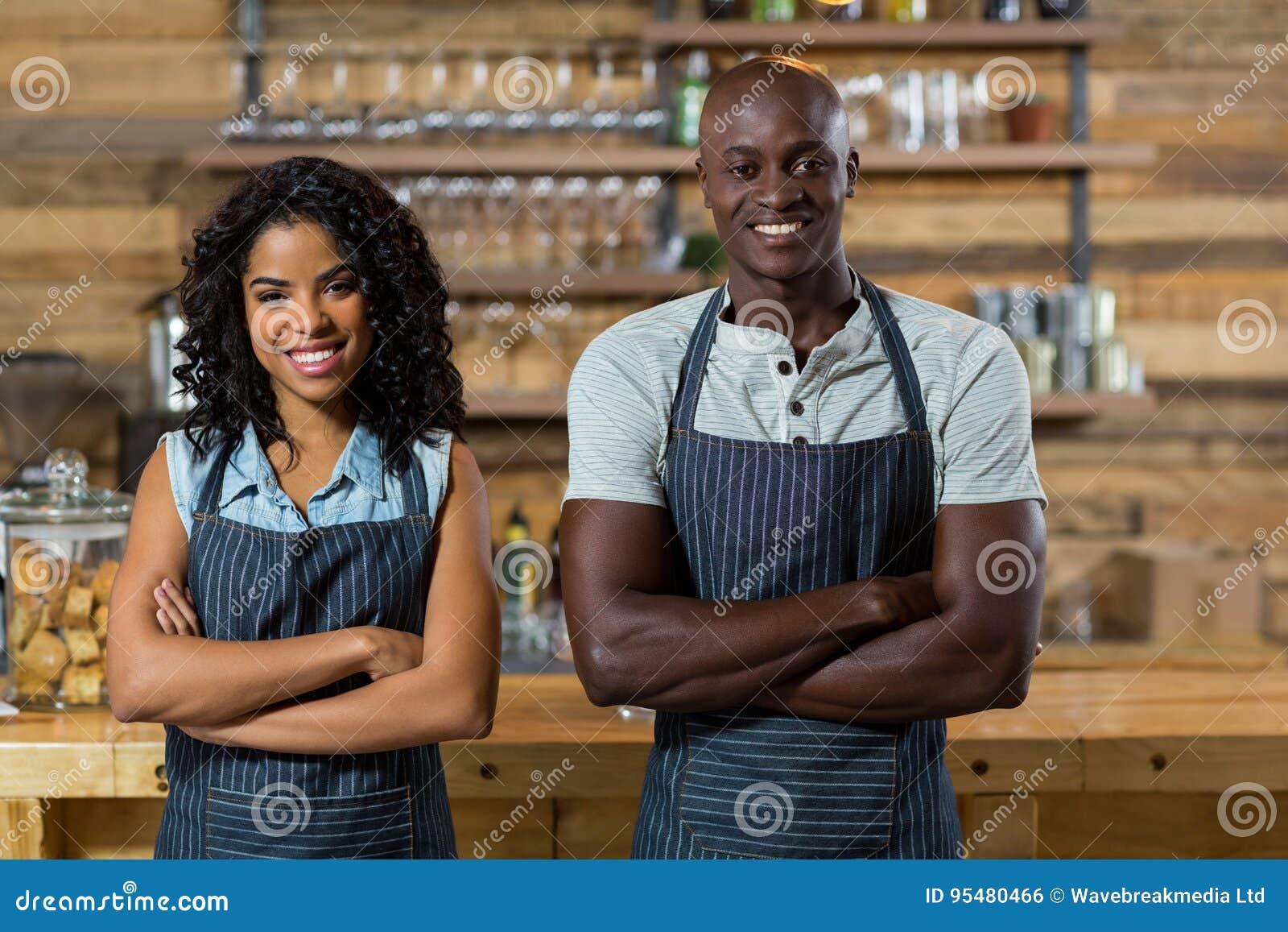 Portret uśmiechnięta kelnera i kelnerki pozycja z rękami krzyżował przy kontuarem