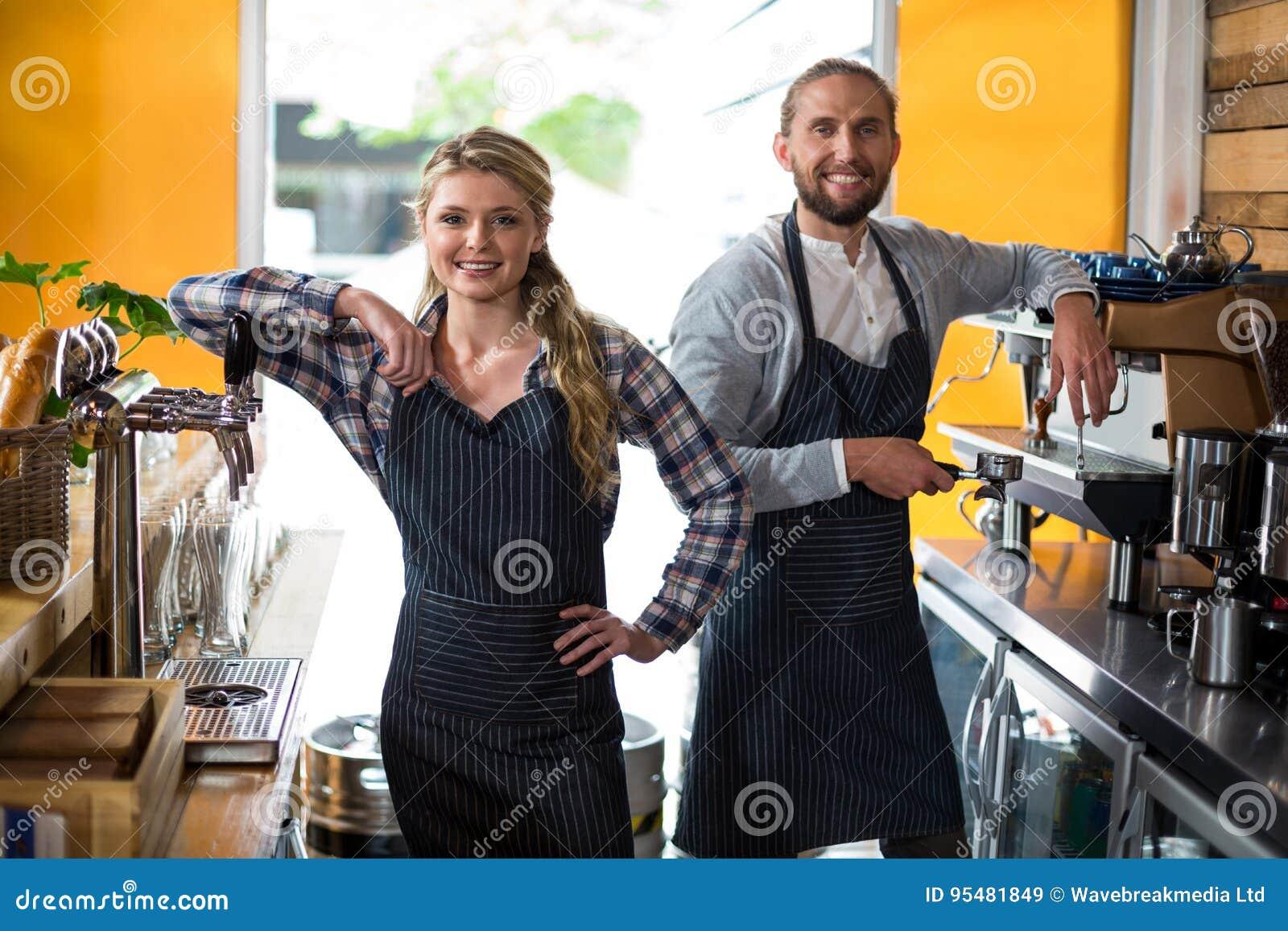 Portret uśmiechnięta kelnerka i kelner pracuje przy kontuarem