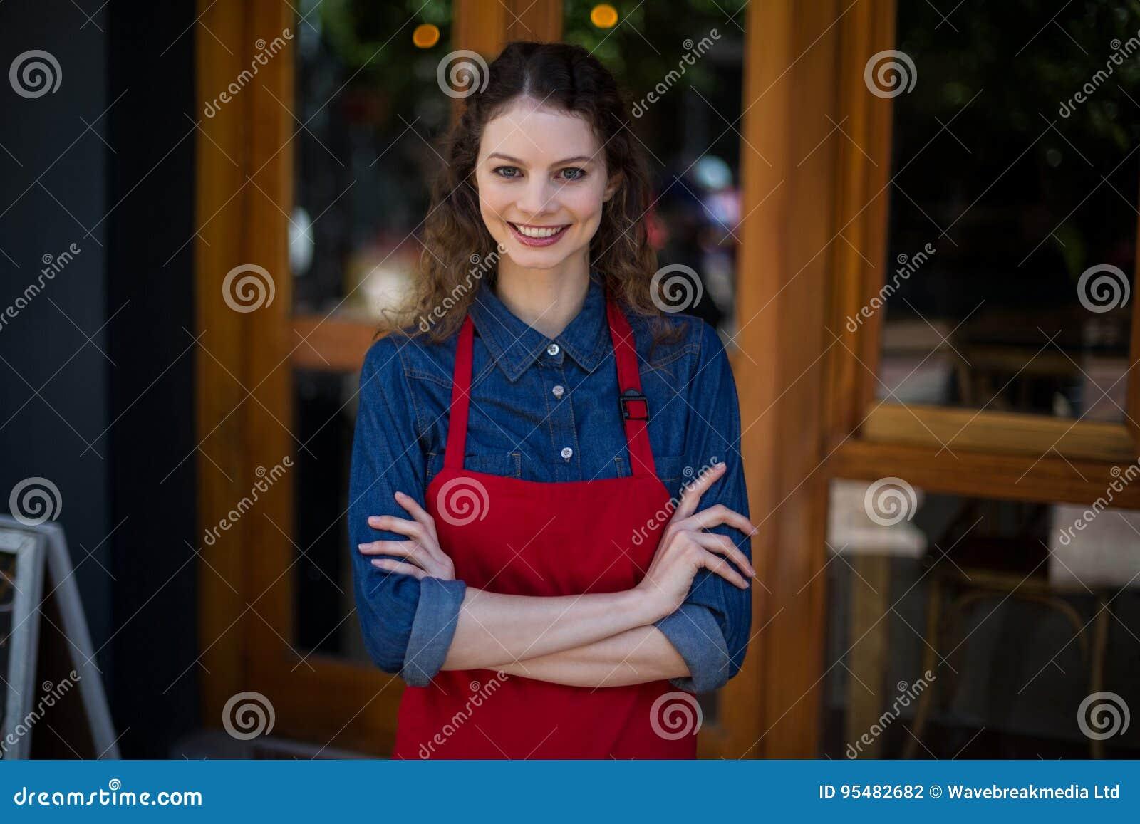 Portret uśmiechnięta kelnerki pozycja z rękami krzyżować