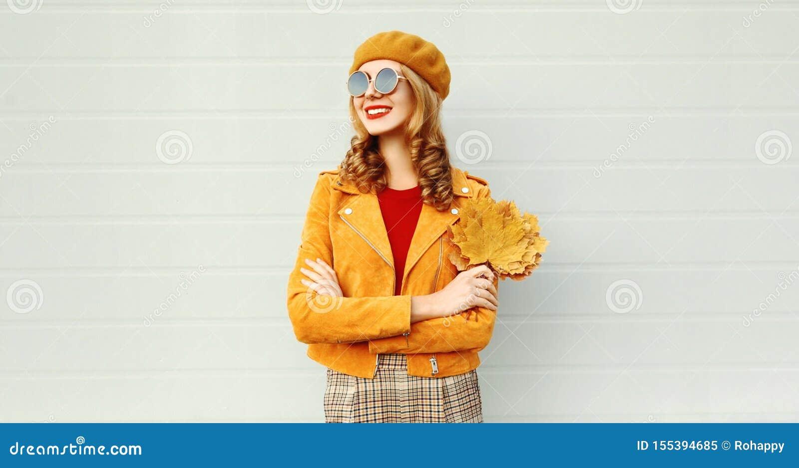 Portret uśmiechnięta kobieta jest ubranym pomarańczowego francuskiego beret na miasto ulicie nad szarości ścianą z żółtymi liśćmi