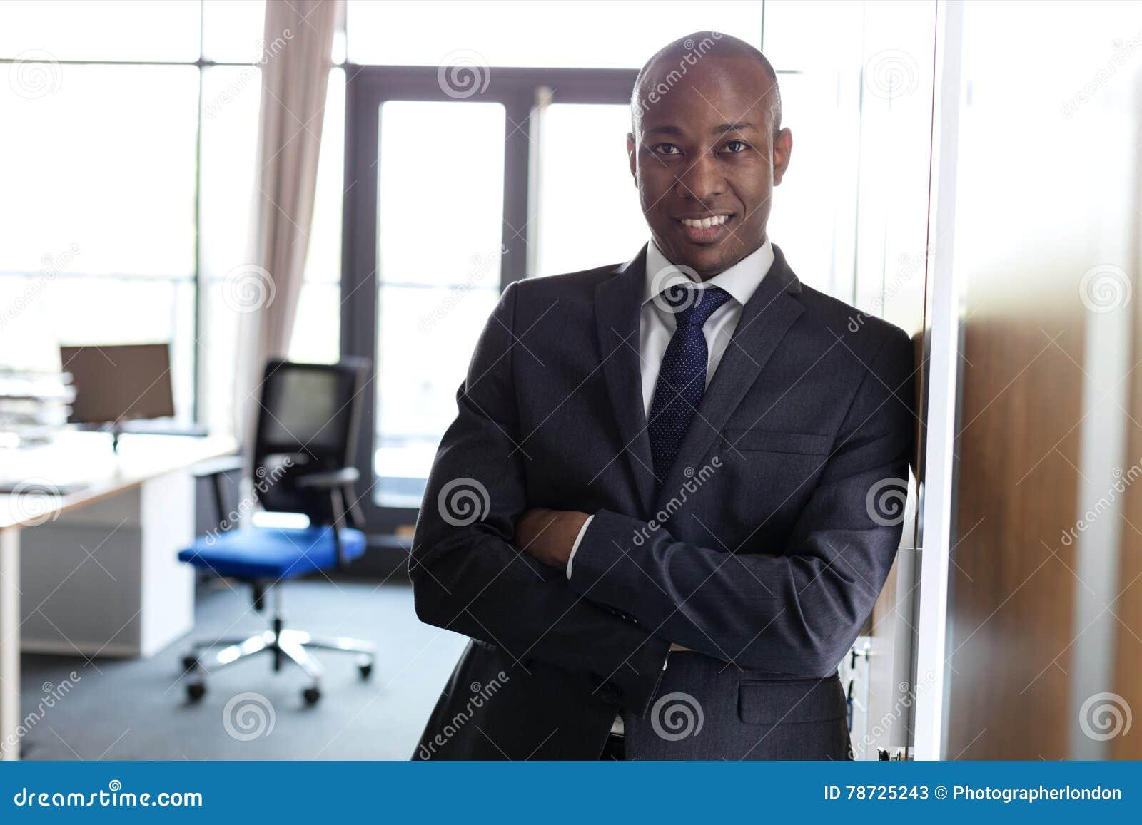 Portret uśmiechnięta młoda biznesmen pozycja zbroi krzyżuję opierać na spiżarni w biurze