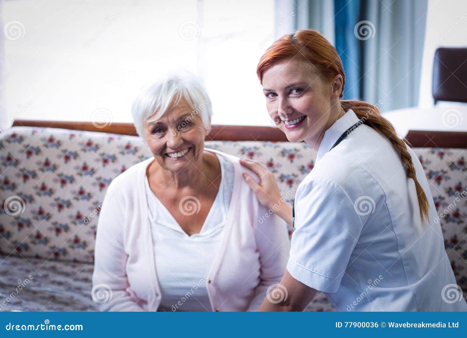 Portret uśmiechnięta starsza kobiety i kobiety lekarka w żywym pokoju