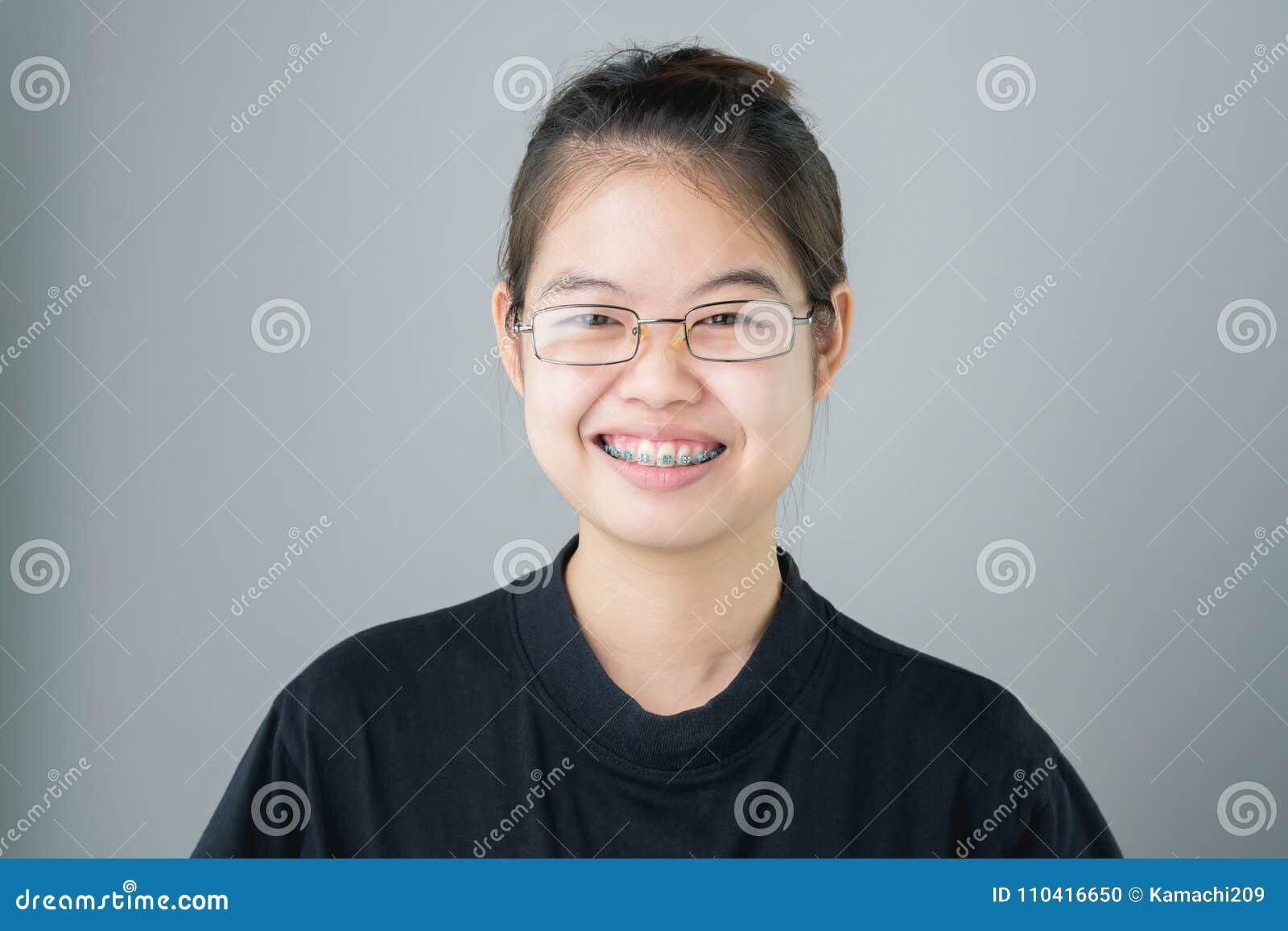 Portret uśmiechnięte azjatykcie młode kobiety stawia dalej brasy na szarości tło daje miękkiemu światłu