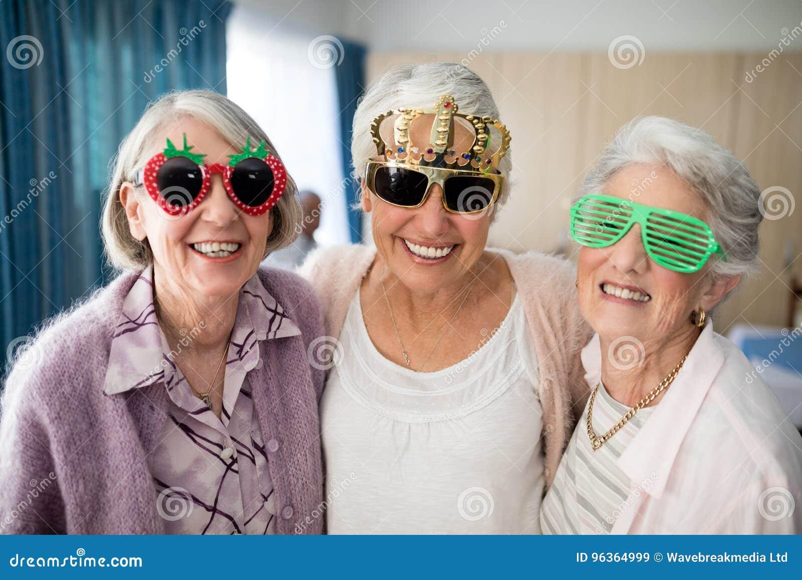 Portret uśmiechnięte starsze kobiety jest ubranym odkrywczość szkła