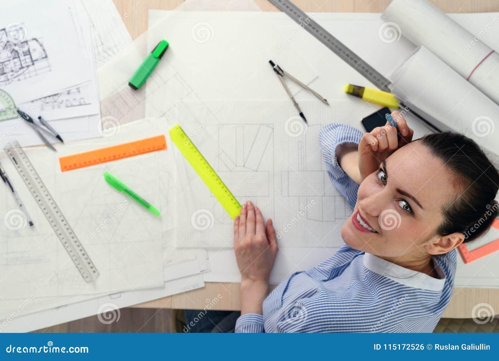 Portret uśmiechnięty żeński architekt na stole z rysunkami, władcy, ołówki, kompasy