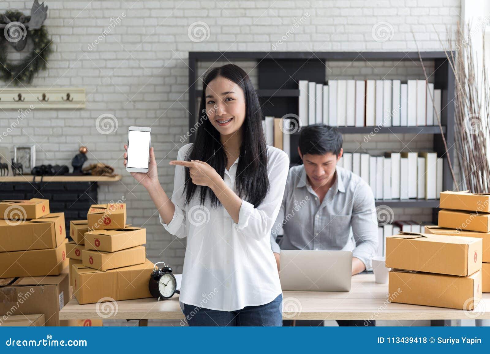 Portret uśmiechnięty azjatykci młoda kobieta chwyta smartphone z kartonów stać