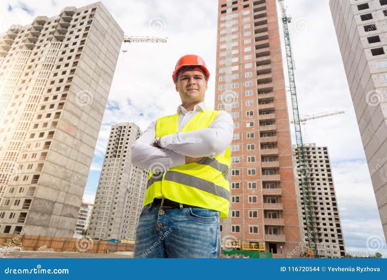 Portret uśmiechnięty młody architekt w hardhat pozuje na placu budowy