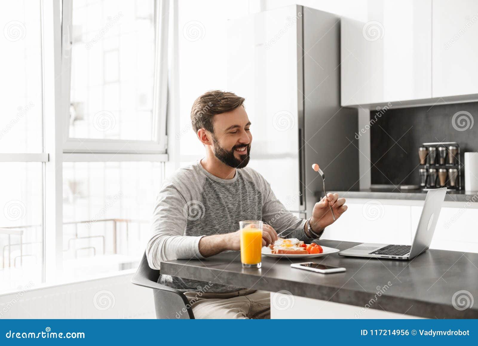Portret uśmiechnięty młody człowiek ma śniadanie