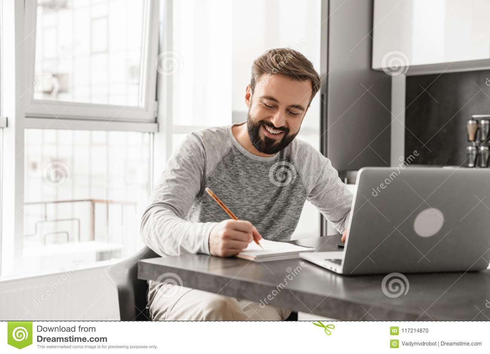 Portret uśmiechnięty młody człowiek pracuje na laptopie