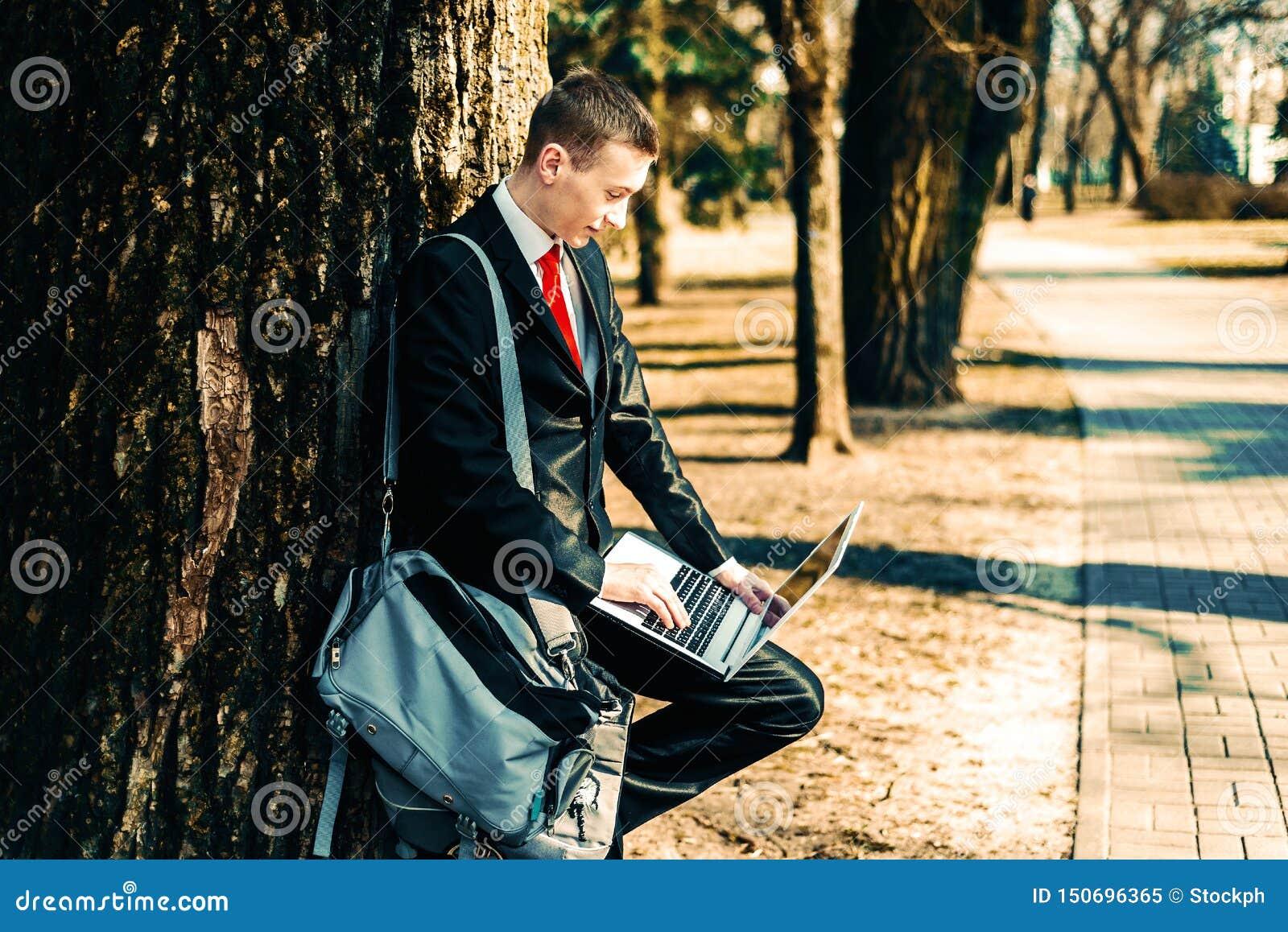 Portret uczeń w czarnym kostiumu czerwonym krawacie na naturze blisko wielkiego drzewa i na ramieniu młoda facet torba freelancer