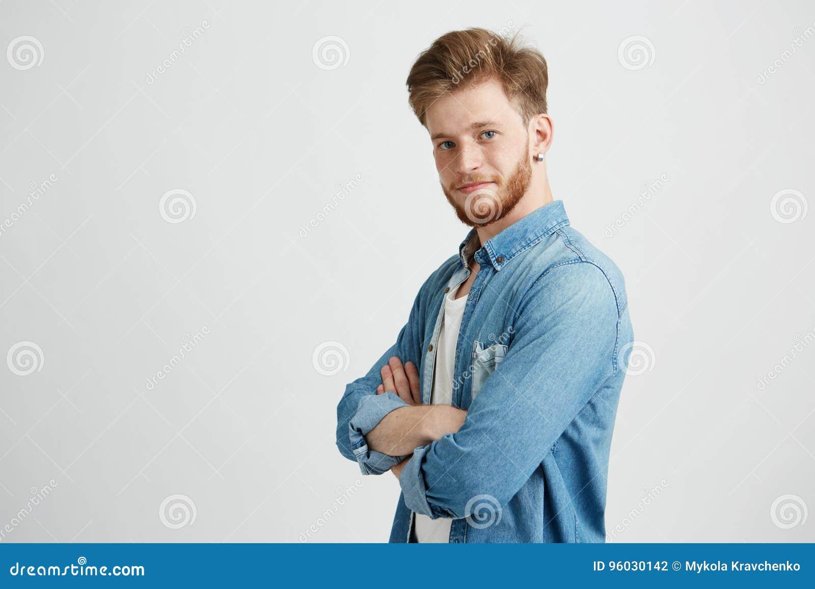 Portret ufny młody przystojny mężczyzna ono uśmiecha się patrzejący kamerę z krzyżować rękami nad białym tłem