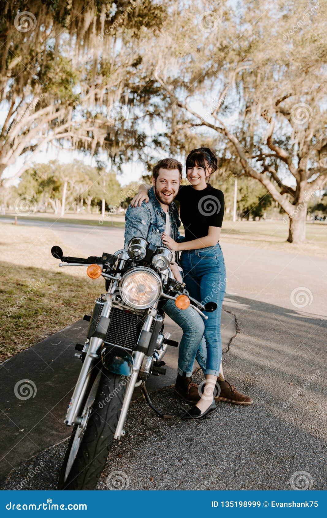 Portret van Aantrekkelijk Knap Jong Modern In Modieus Guy Girl Couple Riding op de Groene Oude School van de Motorfietskruiser